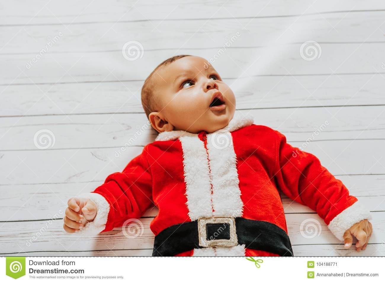 8d1d99cd900c Portrait of cute baby boy lying on white background, wearing Santa Claus`  outfit, looking up