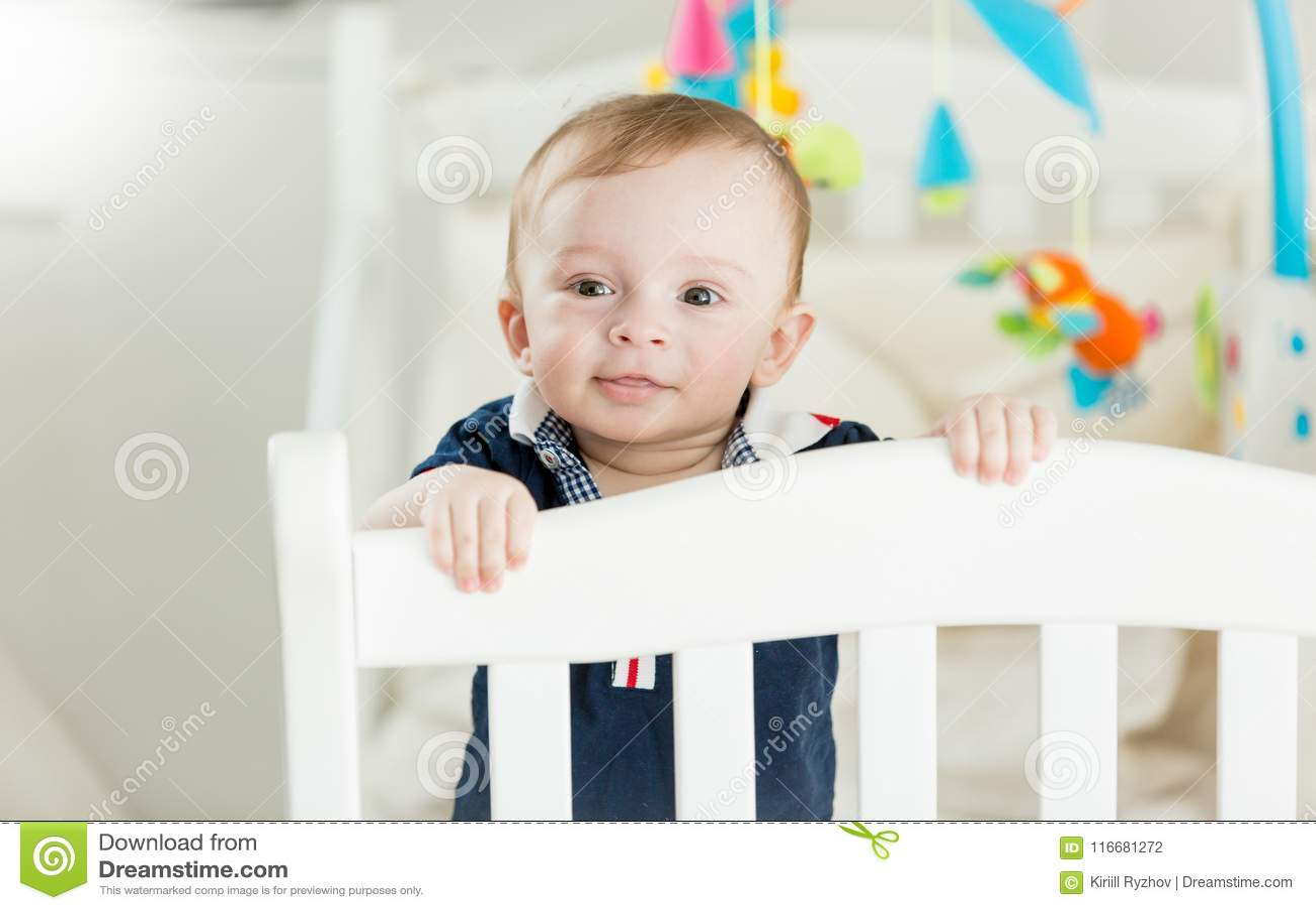 Portrait Of Cute Baby Boy Standing In White Wooden Crib ...