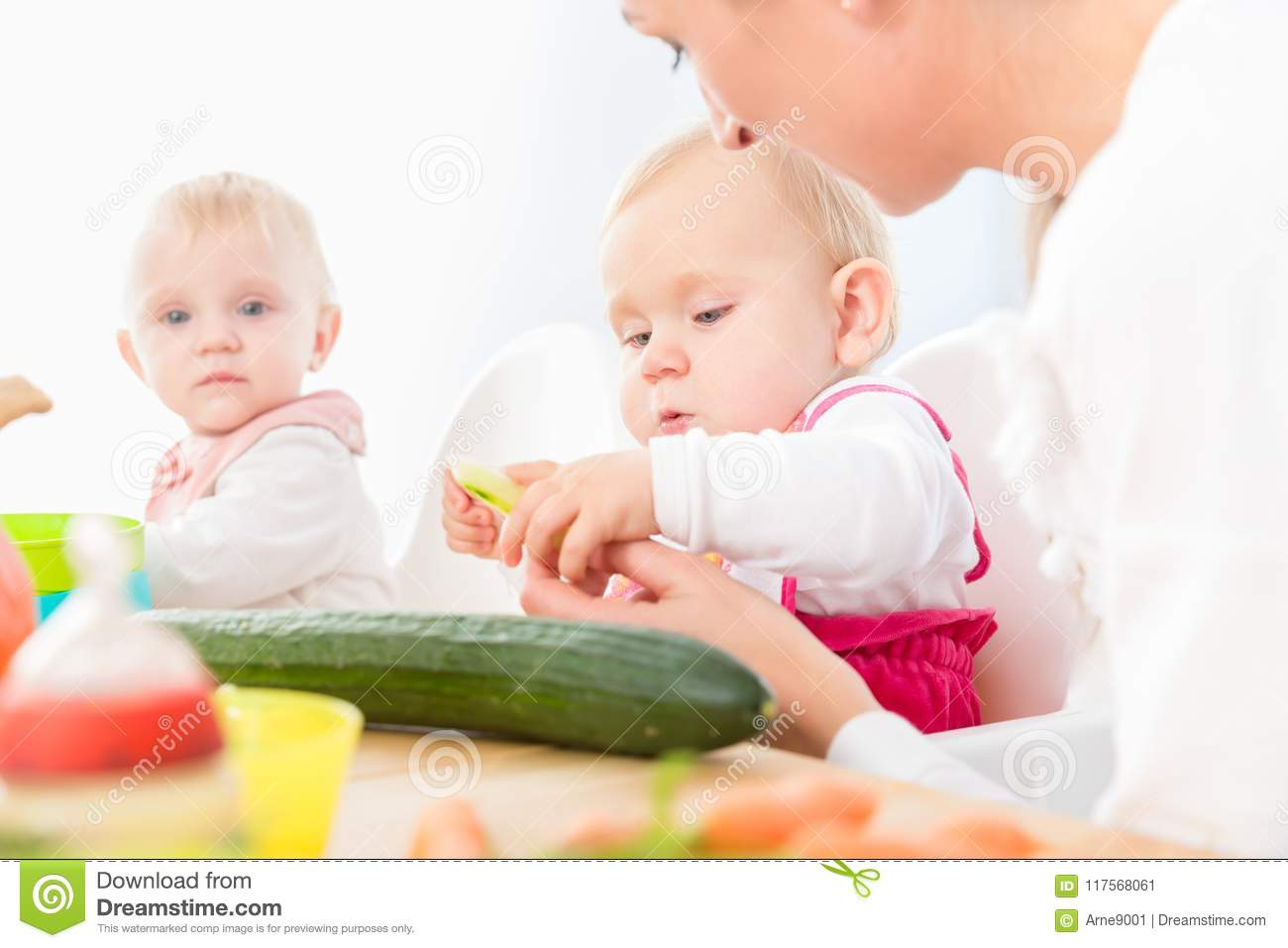 Cute baby girl eating healthy solid food in a modern daycare center