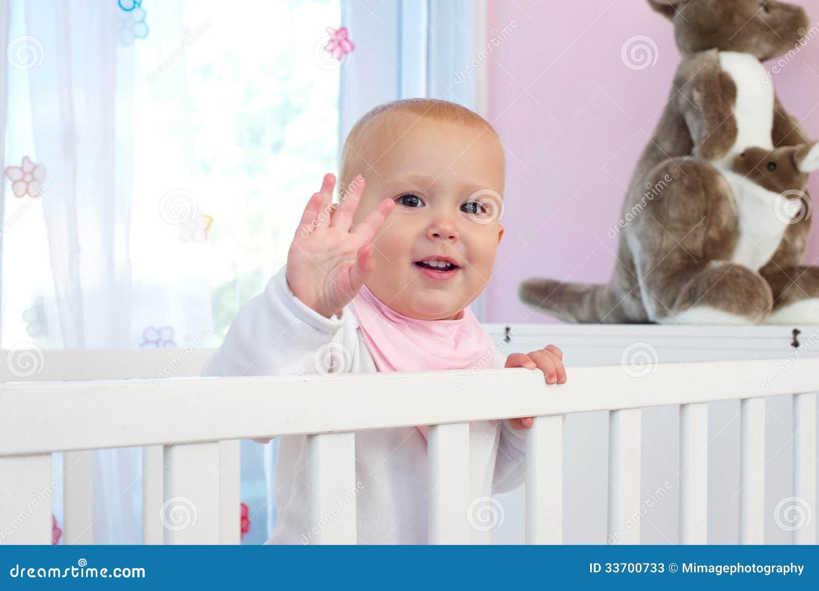 Child waving hello smiling and waving hello