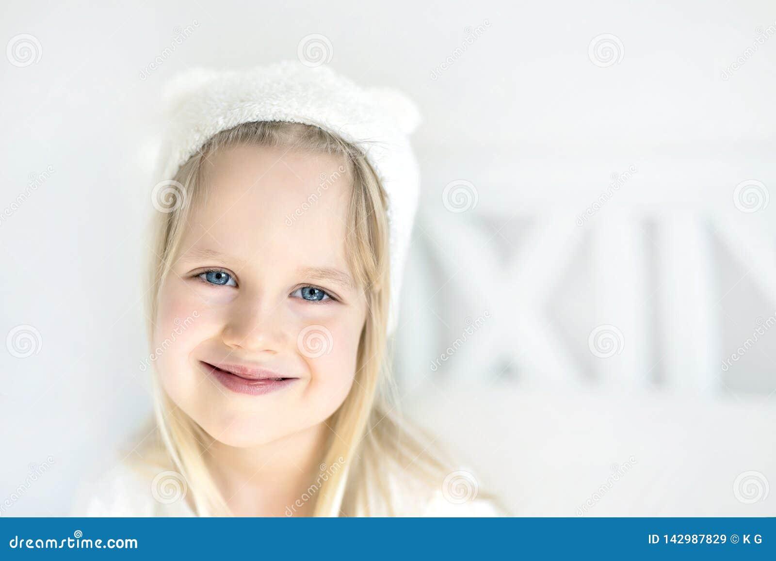 Portrait cute blond preschooler girl. Smilling kid in white hat. Child on bed in nursery room. Adorable baby wearing funny hat