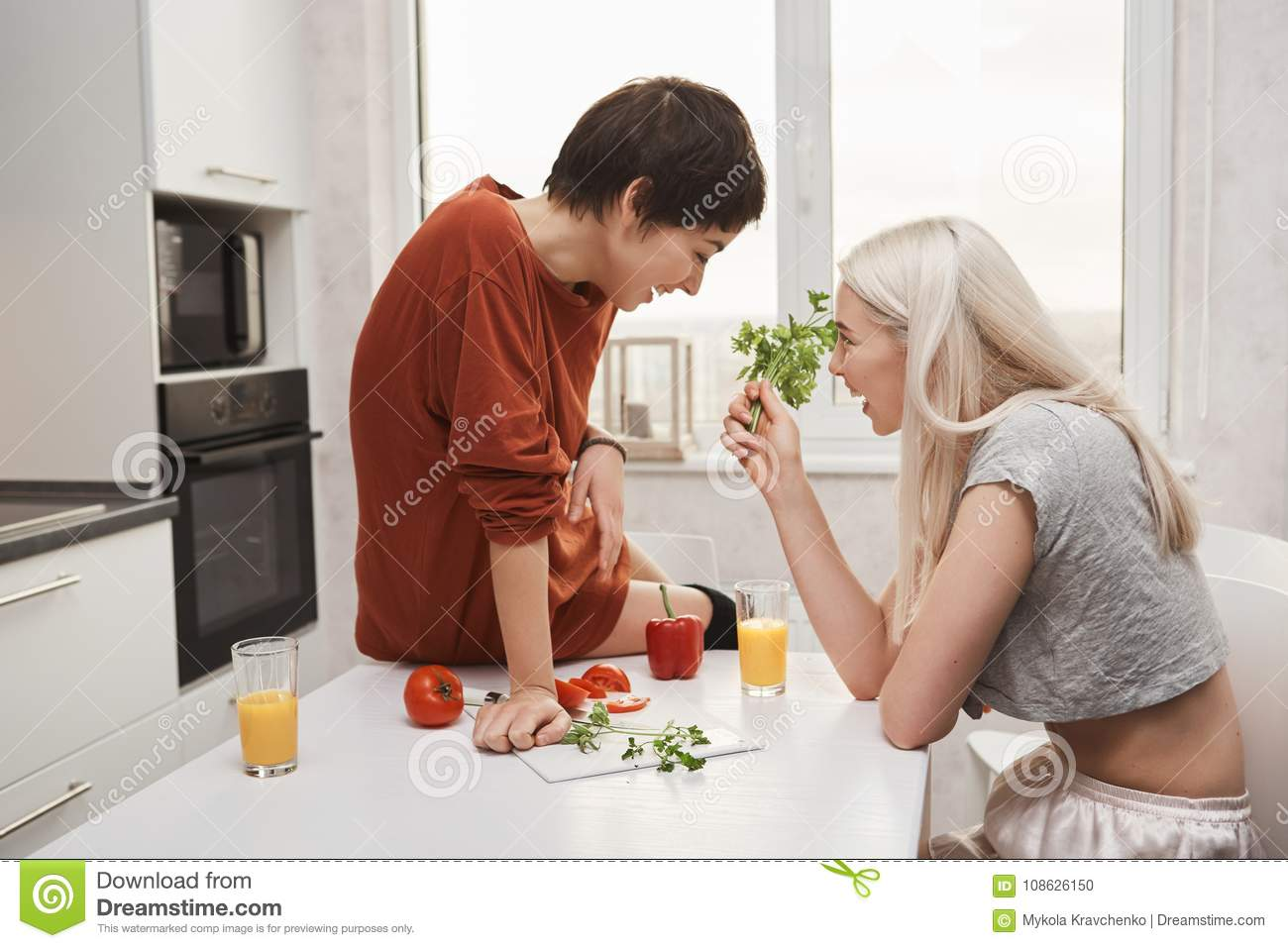 Portrait of cute blonde girl holding salary and talking to her girlfriend while she sits on kitchen table and laughs