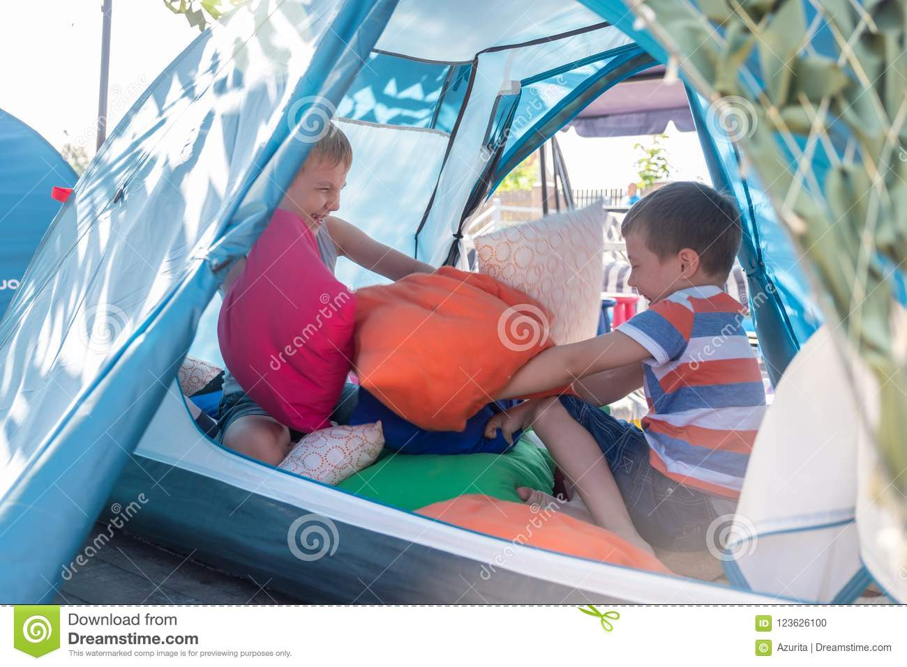 Cute boys playing with pillow inside tent at backyard & Portrait Of Cute Boy Inside Tent At Backyard Stock Photo - Image of ...