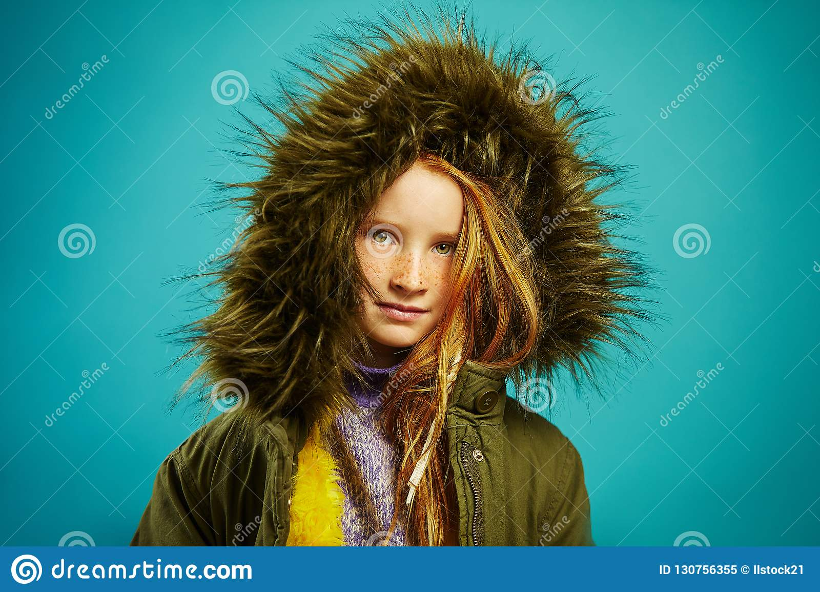 Portrait of cute child girl wears stylish jacket with hood on blue background.