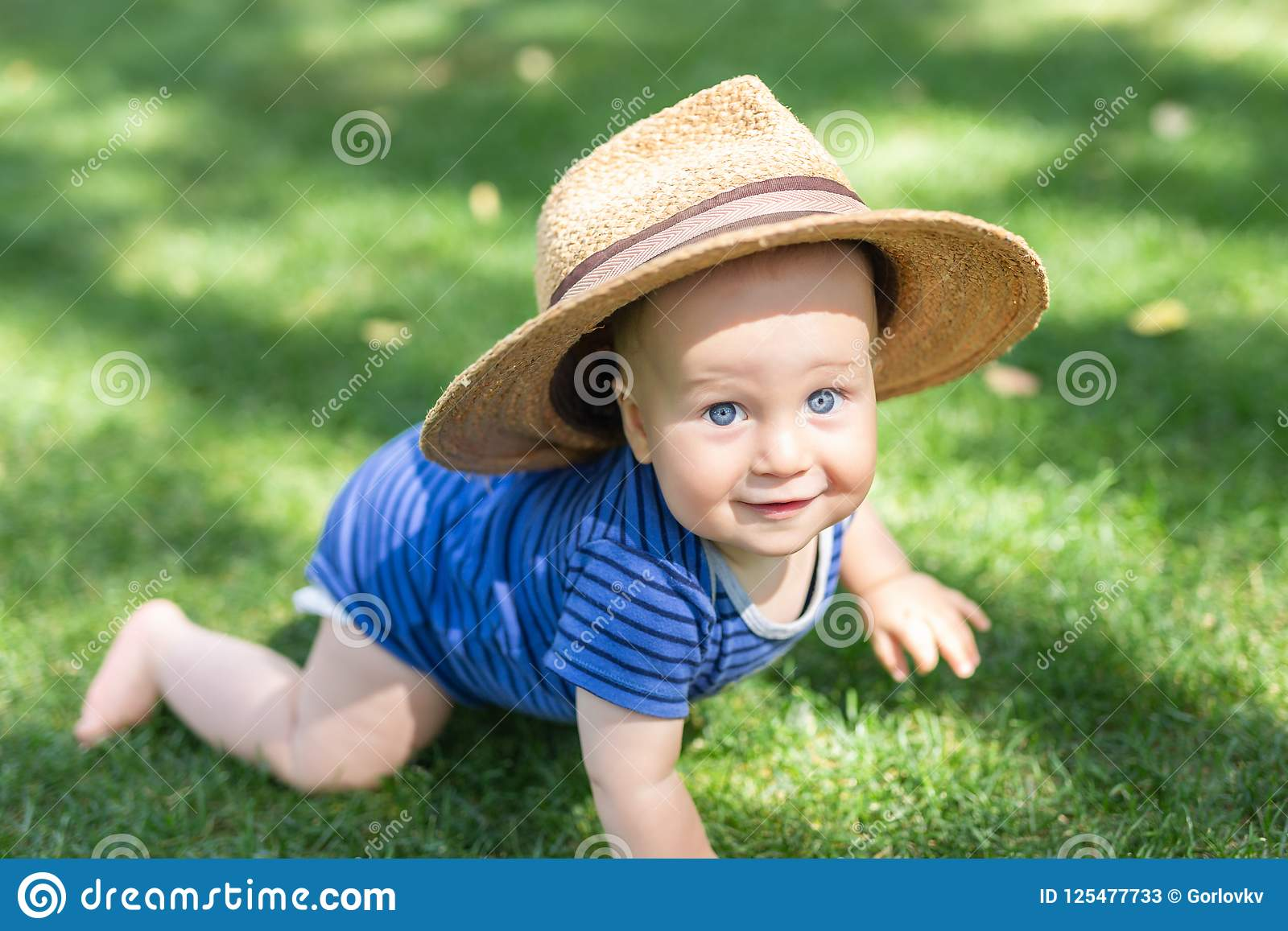 Portrait cute funny little boy in big straw hat having fun on green grass lawn at park. Sweet little baby crawling and smiling at