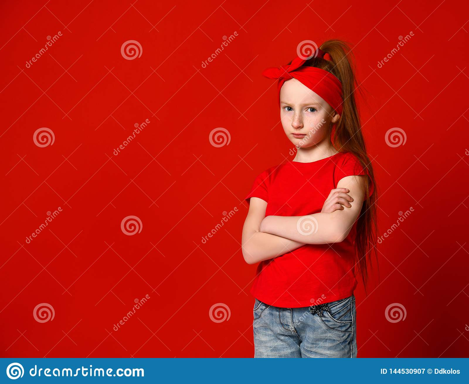 Portrait of a cute girl upset in a red vest, standing with folded hands and looking at camera