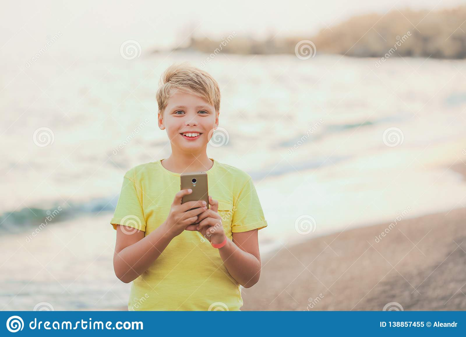 Portrait of cute happy smiling white kid using modern smart phone