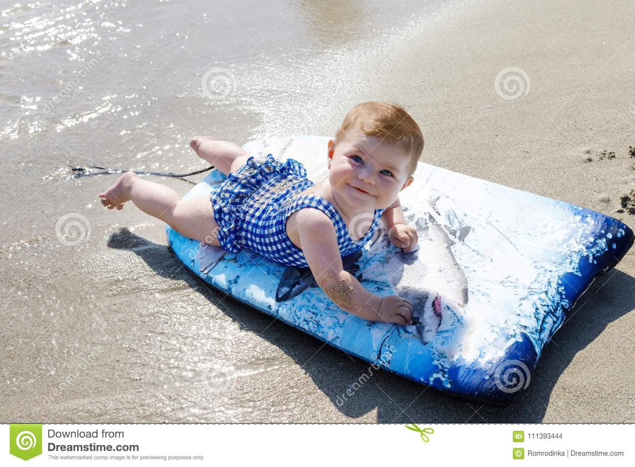 1cbf5f64aa99 Portrait of cute little baby girl in swim suit on beach in summer. Adorable  child having fun on surf board. Baby fashion for swimsuit.