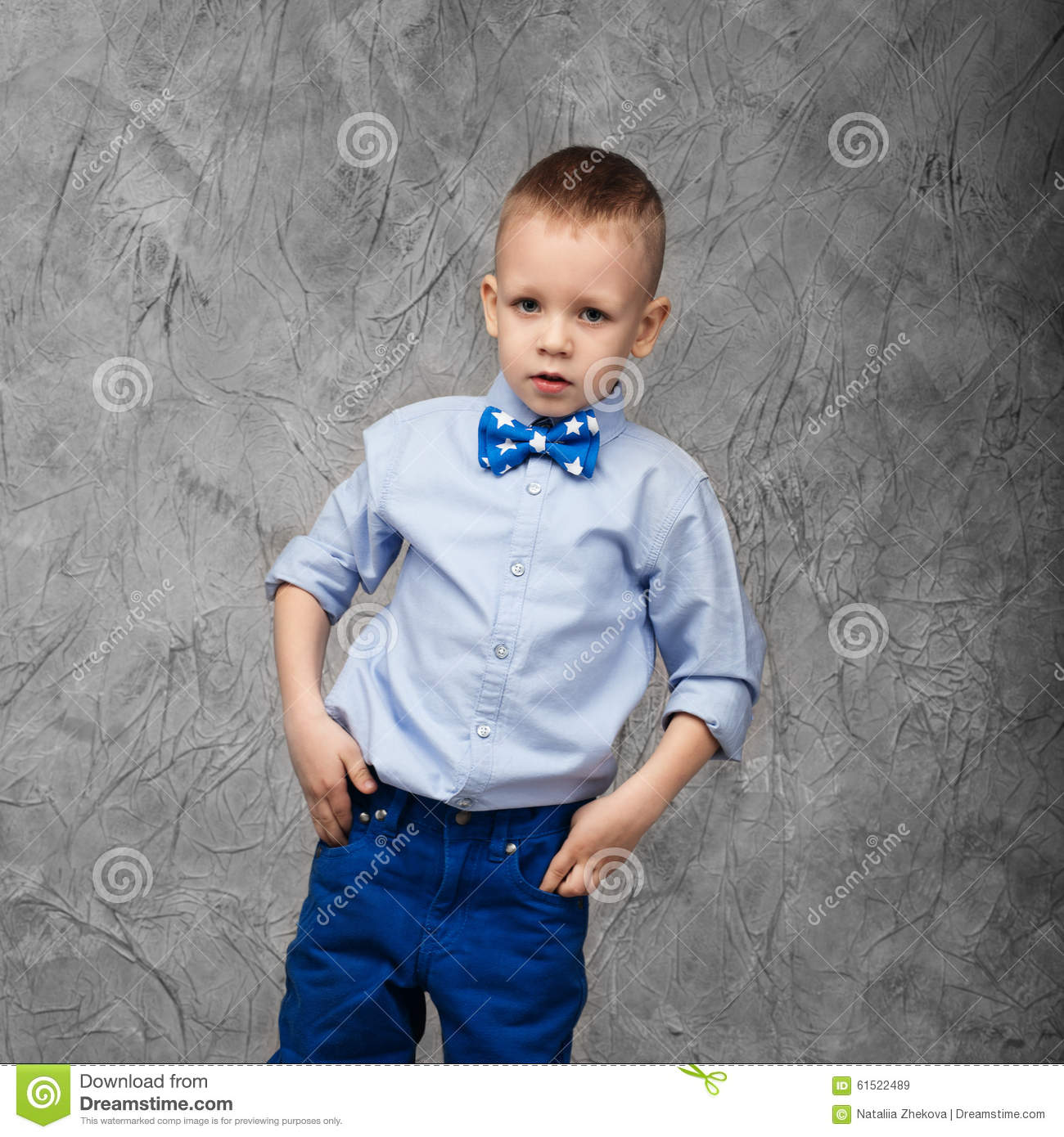 portrait of a cute little boy in jeans blue shirt and bow