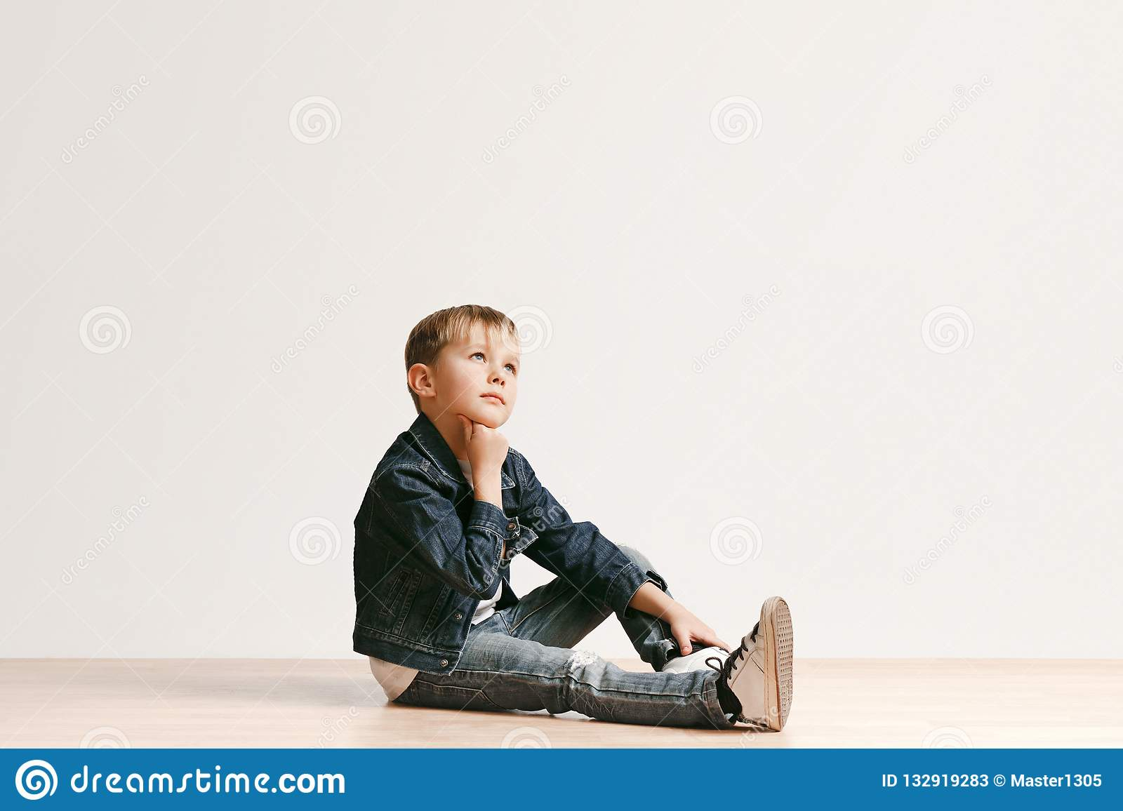 The portrait of cute little kid boy in stylish jeans clothes looking at camera against white studio wall kids fashion concept