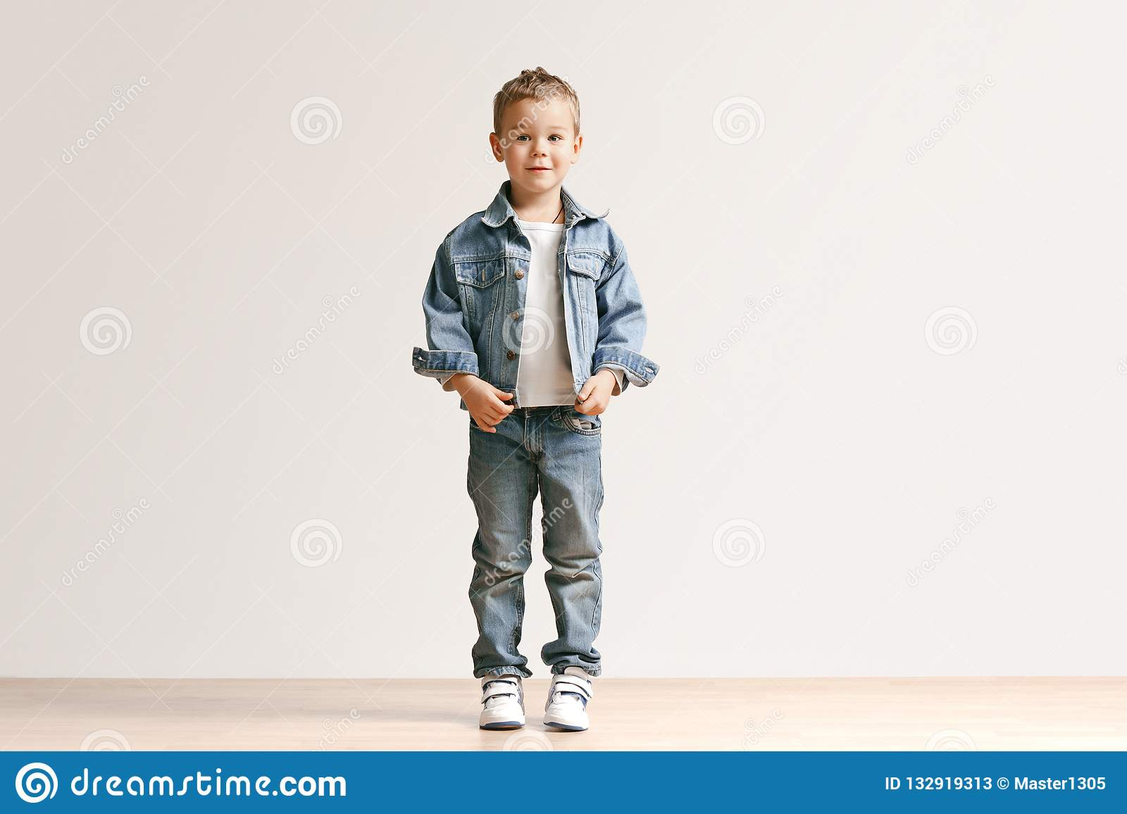 a8257a2f5 The portrait of cute little boy in stylish jeans clothes looking at camera  at studio