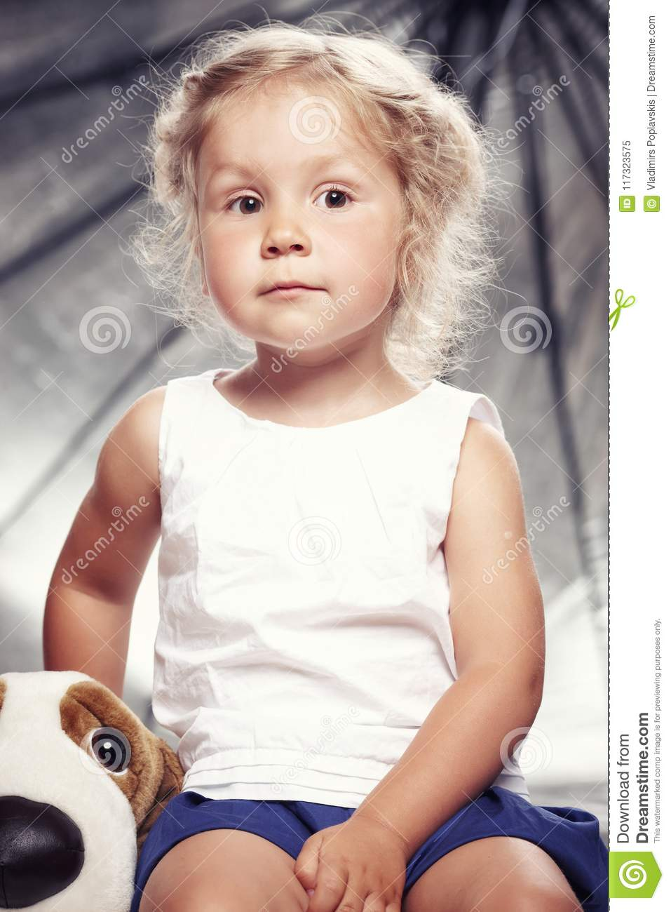 Portrait of a cute little girl in casual dress sitting with a plush toy in studio.