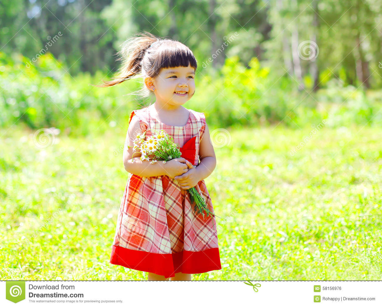 portrait of cute little girl child smiling with flowers stock photo