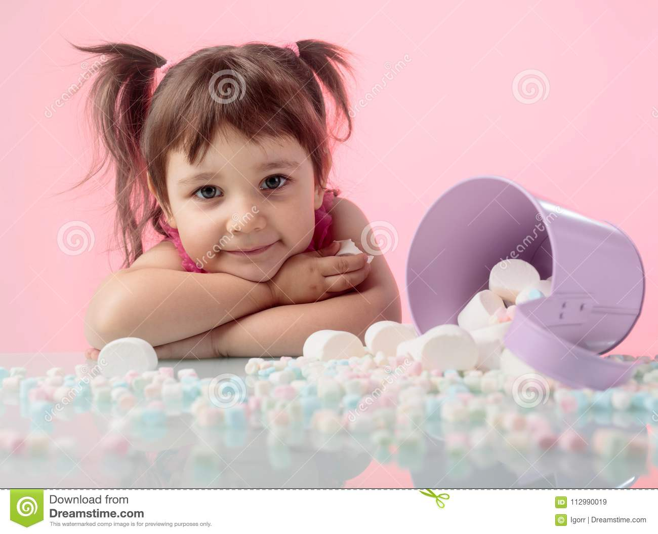 Portrait of a cute little girl with marshmallow on pink background.