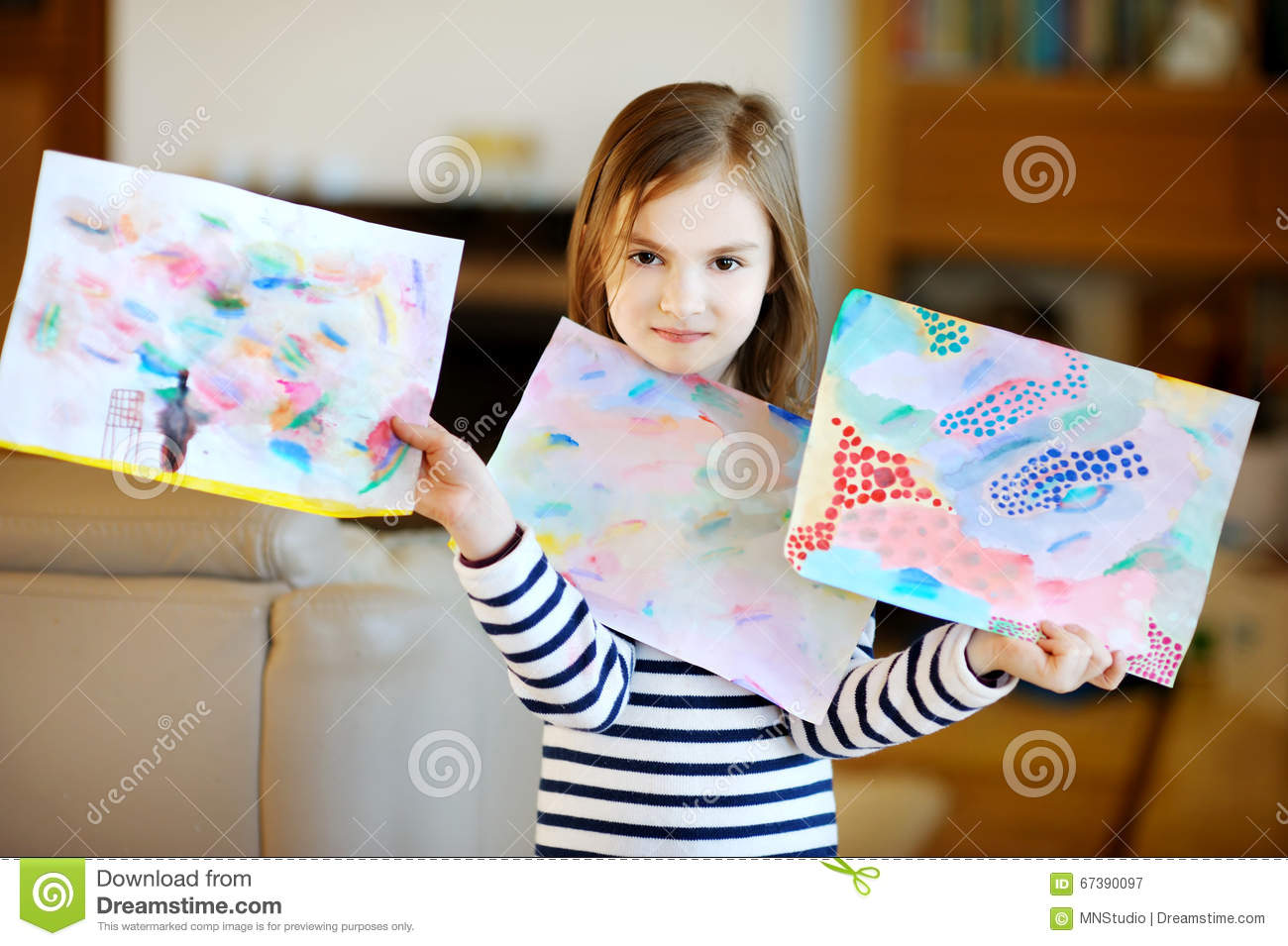 Portrait of cute little girl showing her drawings