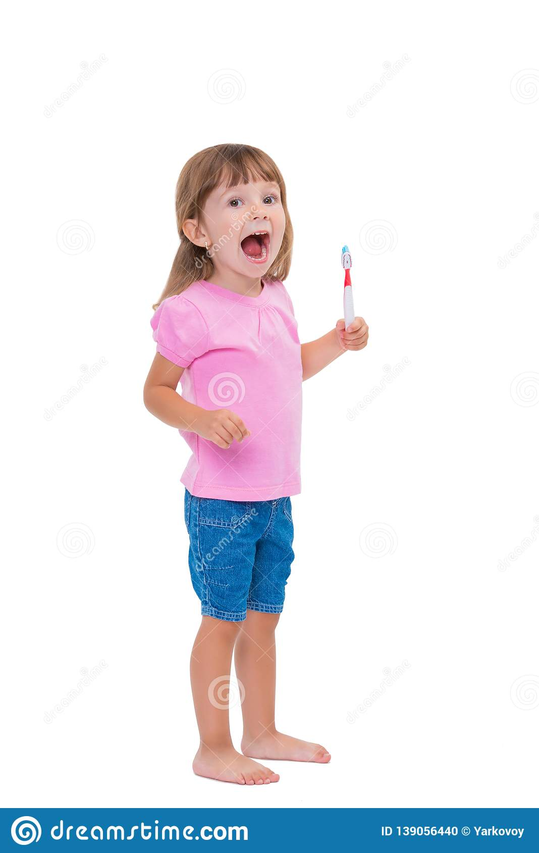 Portrait of cute little girl 3 year old in pink t-shirt brushing her teeth isolated on white background