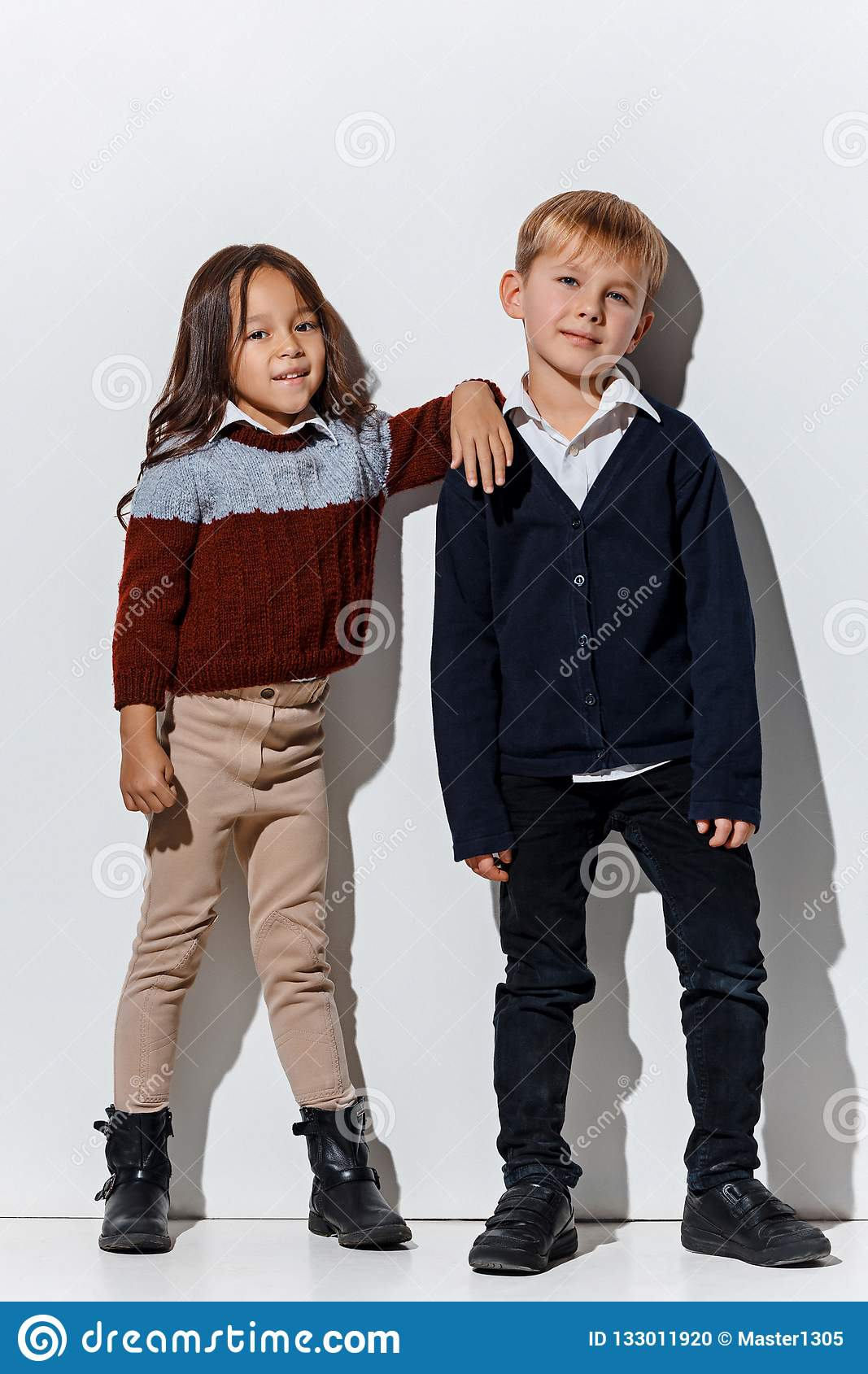 d8440a619 The portrait of cute little kids boy and girl in stylish jeans clothes  looking at camera against white studio wall. Kids fashion and happy  emotions concept