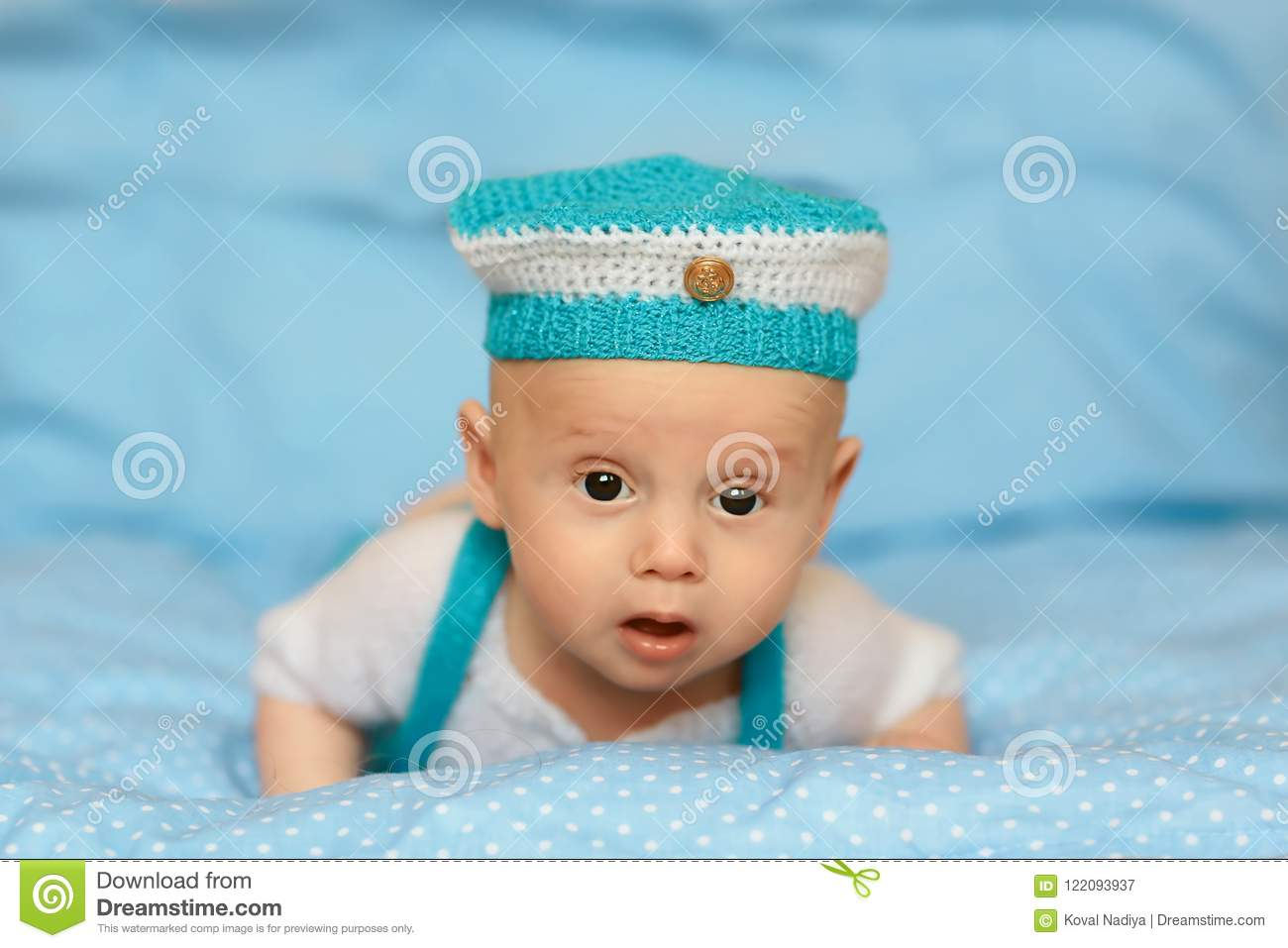 Portrait of a cute 3 months baby lying down in a blue hat on a blanket