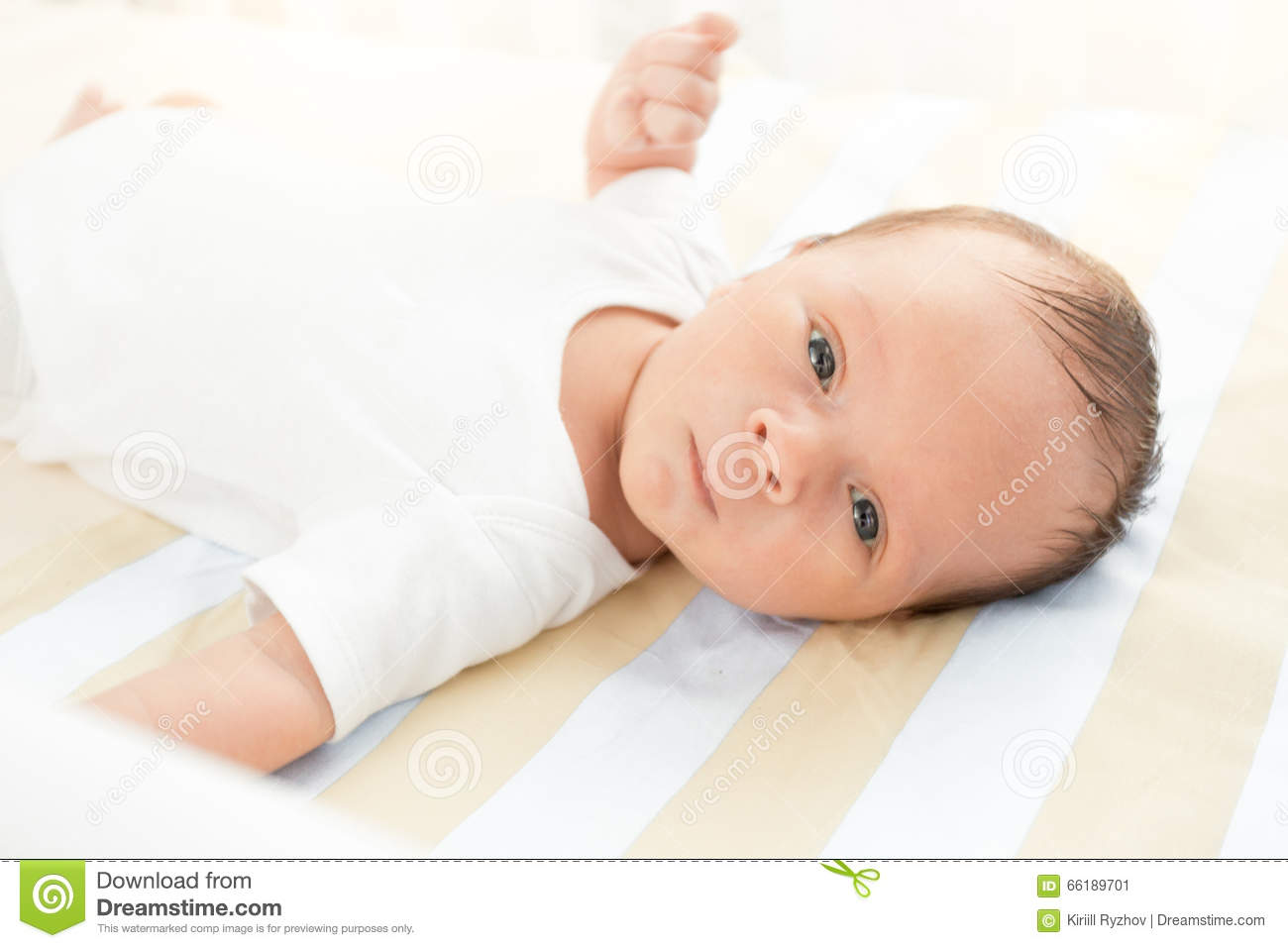 Portrait of cute newborn baby lying in bed and looking at camera