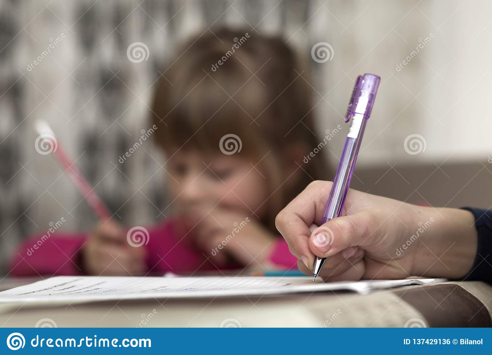 Portrait of cute pretty little serious child girl drawing with pencil on paper on blurred background. Art education, creativity,