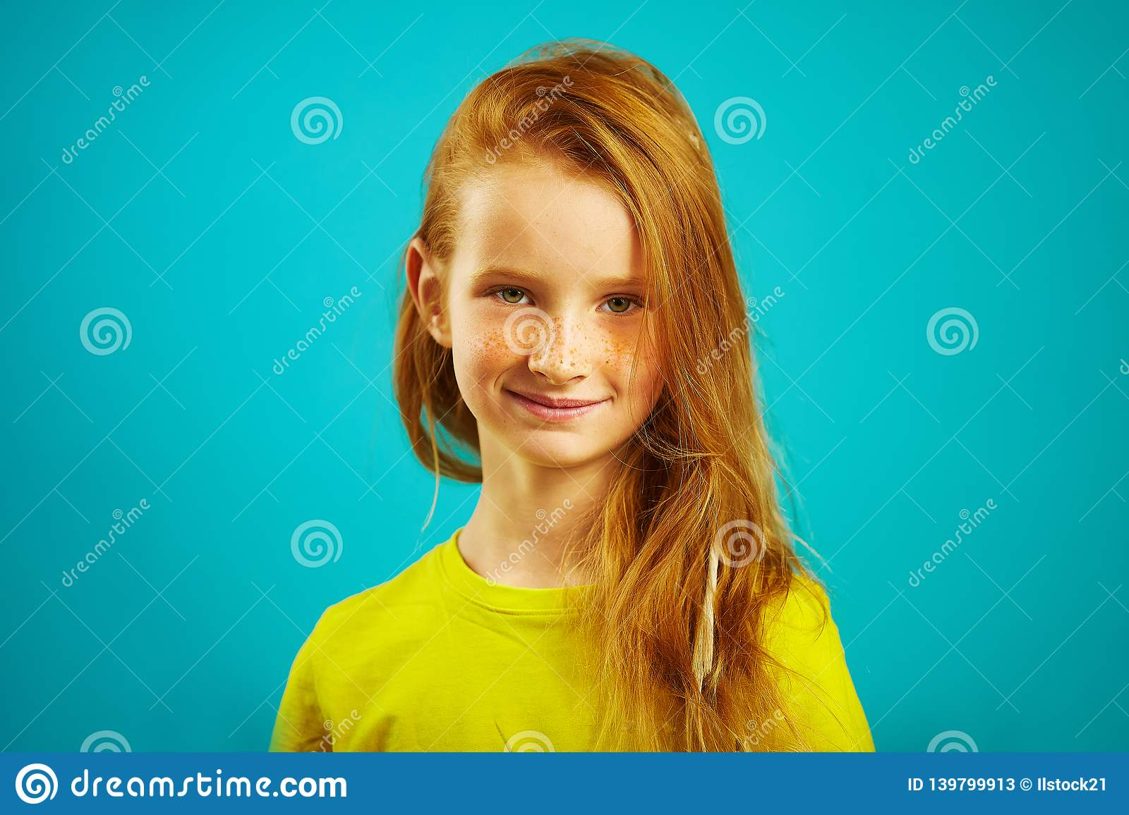 Portrait of cute seven years old girl with red hair and beautiful freckles, wears yellow t-shirt, expresses sincere