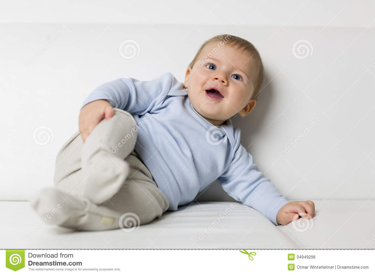 Portrait of cute smiling baby boy lying on sofa stock for Baby boy blue shirt