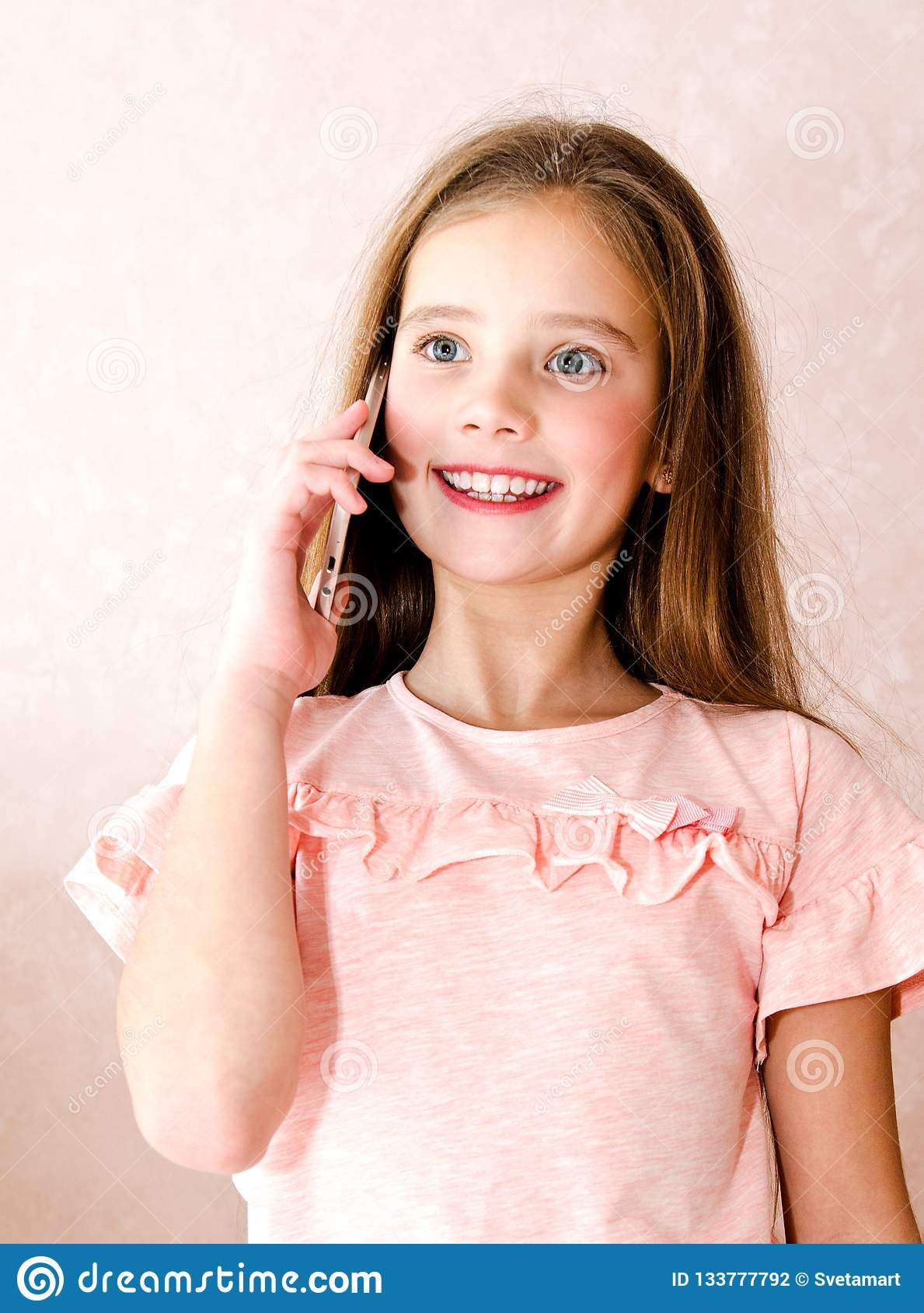 Portrait of cute smiling little girl calling by cell phone smar