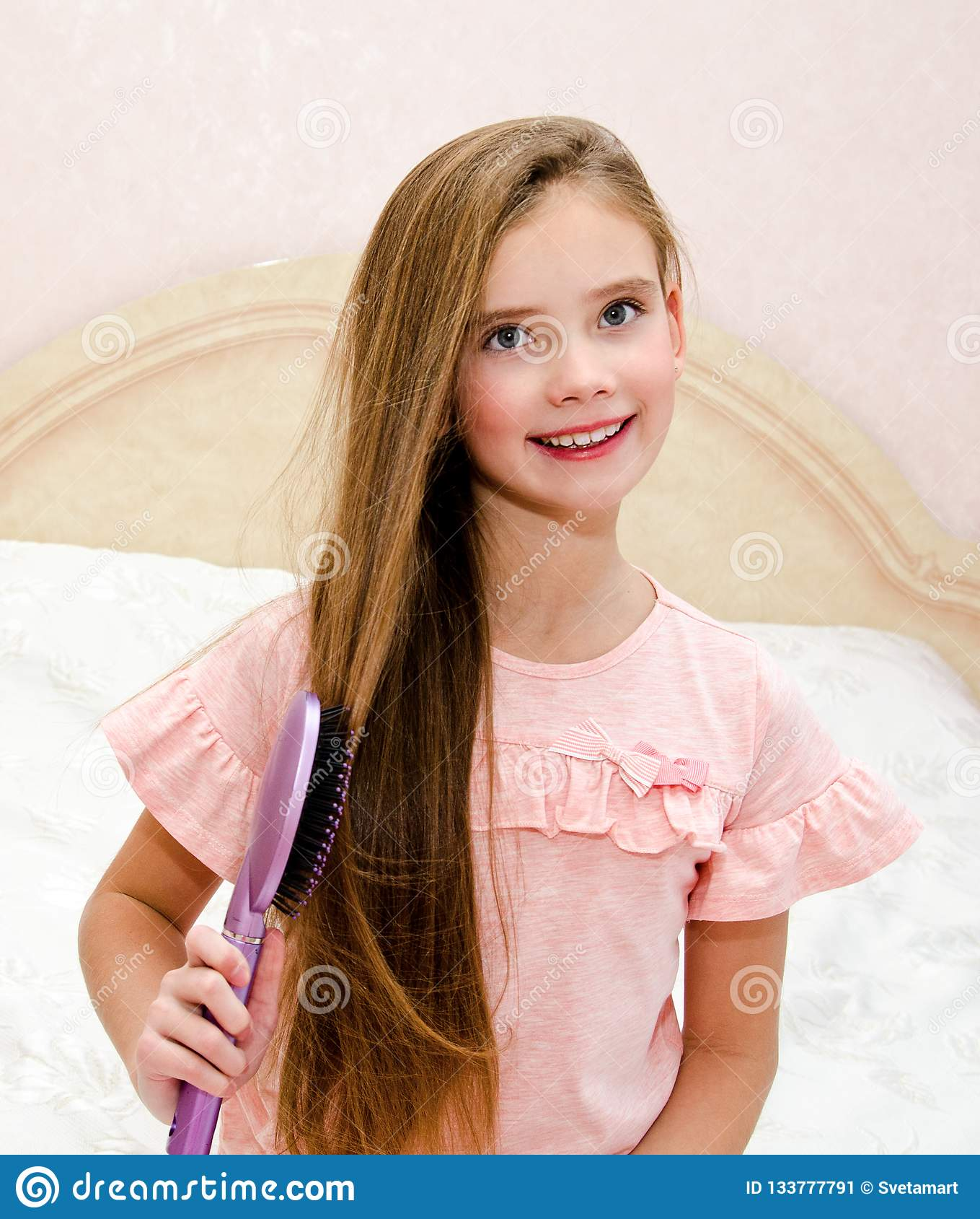 Portrait of cute smiling little girl child brushing her hair