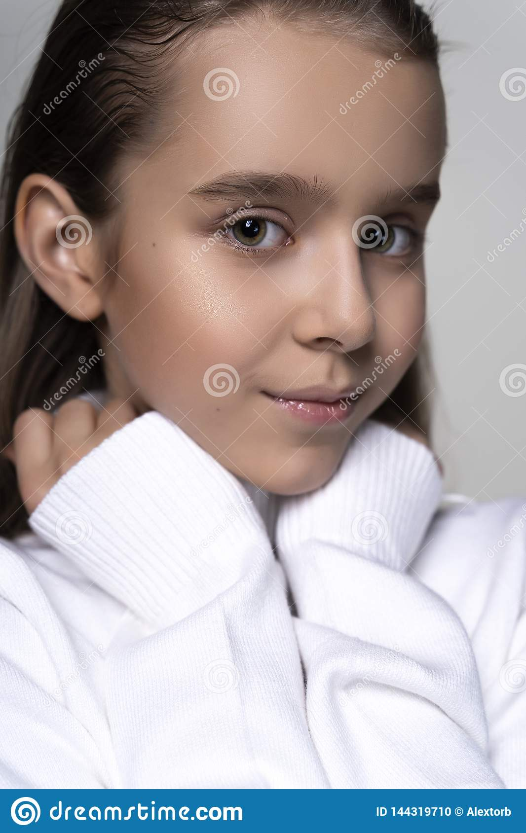 Portrait of a cute smiling teen girl wearing a white turtleneck sweater. on gray background. Advertising, trendy and