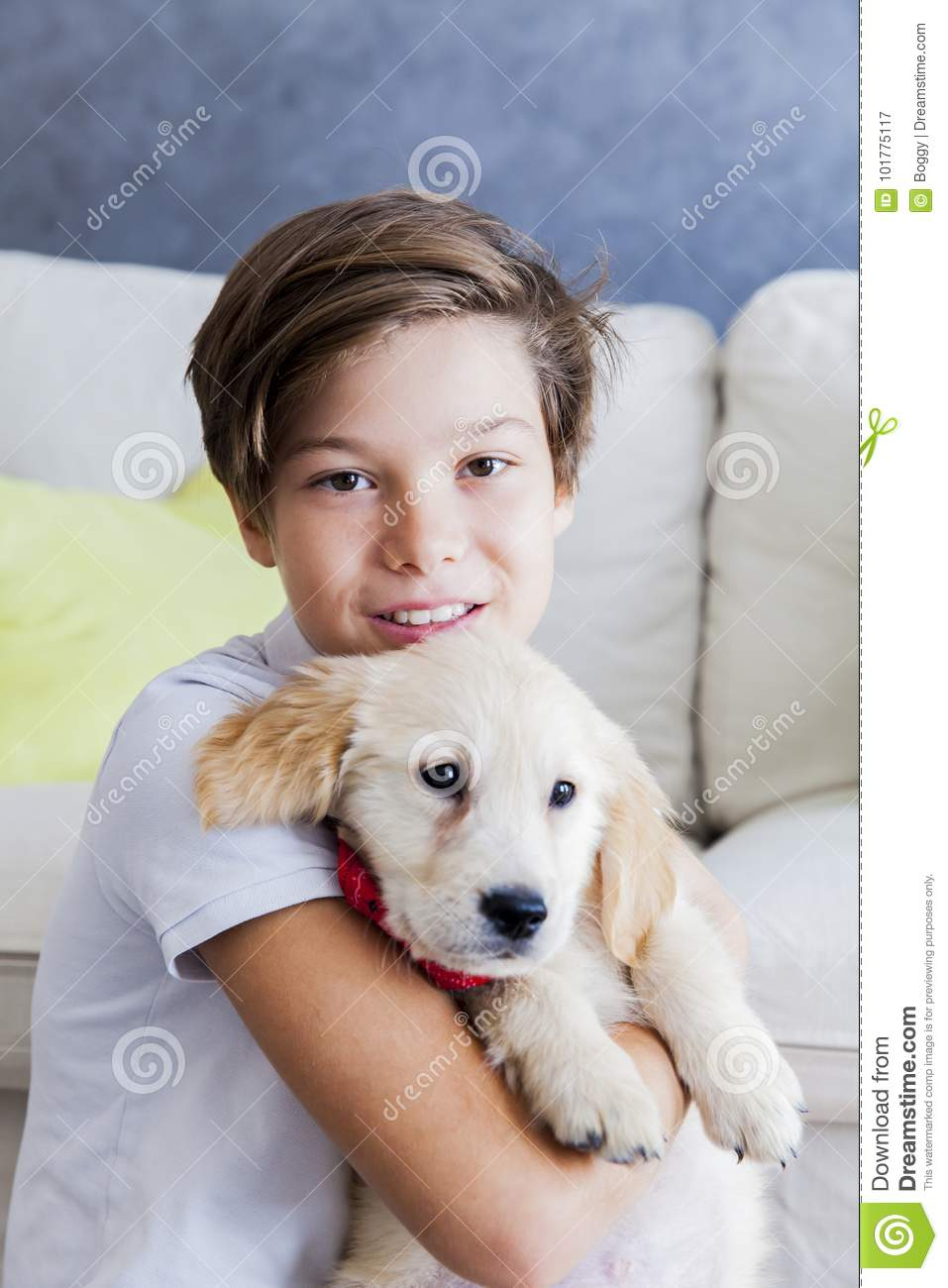 Cute teen boy with baby retriever dog in room