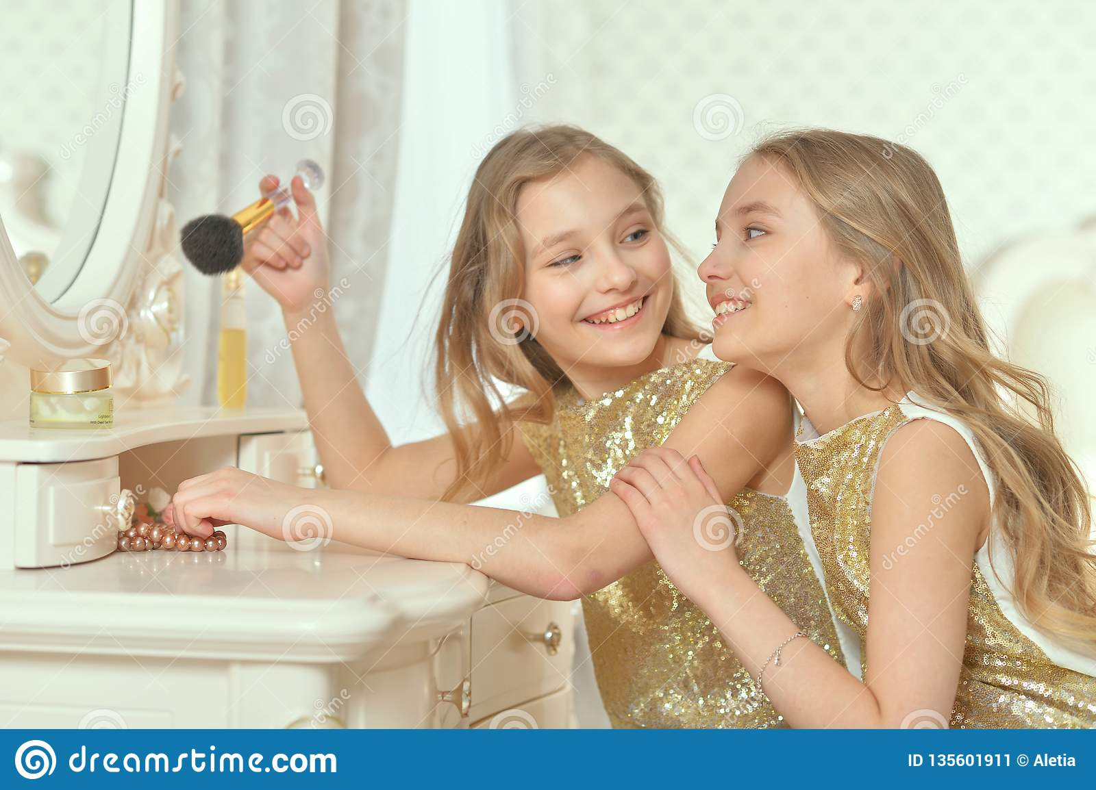 Portrait of cute sisters in golden dresses sitting near dressing table