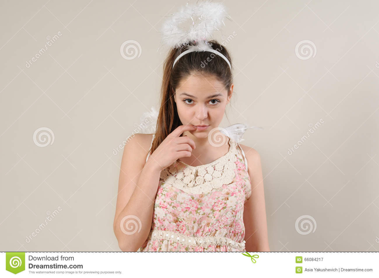 Portrait of cute very shy angel girl with finger near her mouth
