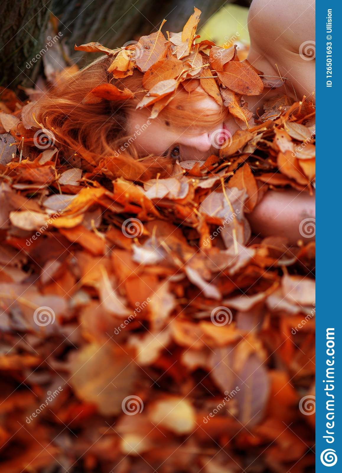 Portrait of a cute young lovely girl covered with red and orange autumnal leaves. Beautiful girl lying on autumn leaves.