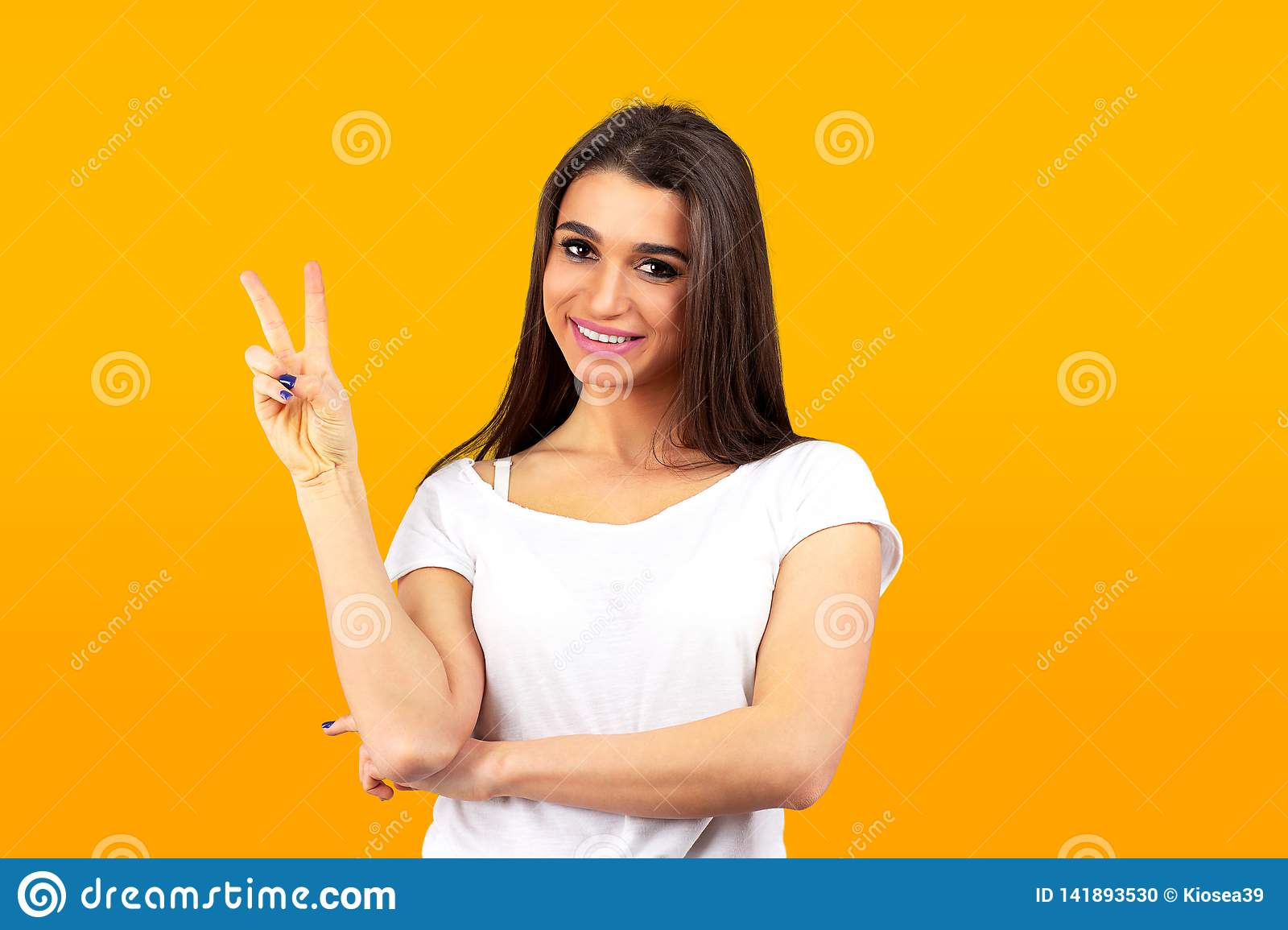 Cute young woman standing looking at camera showing peace gesture