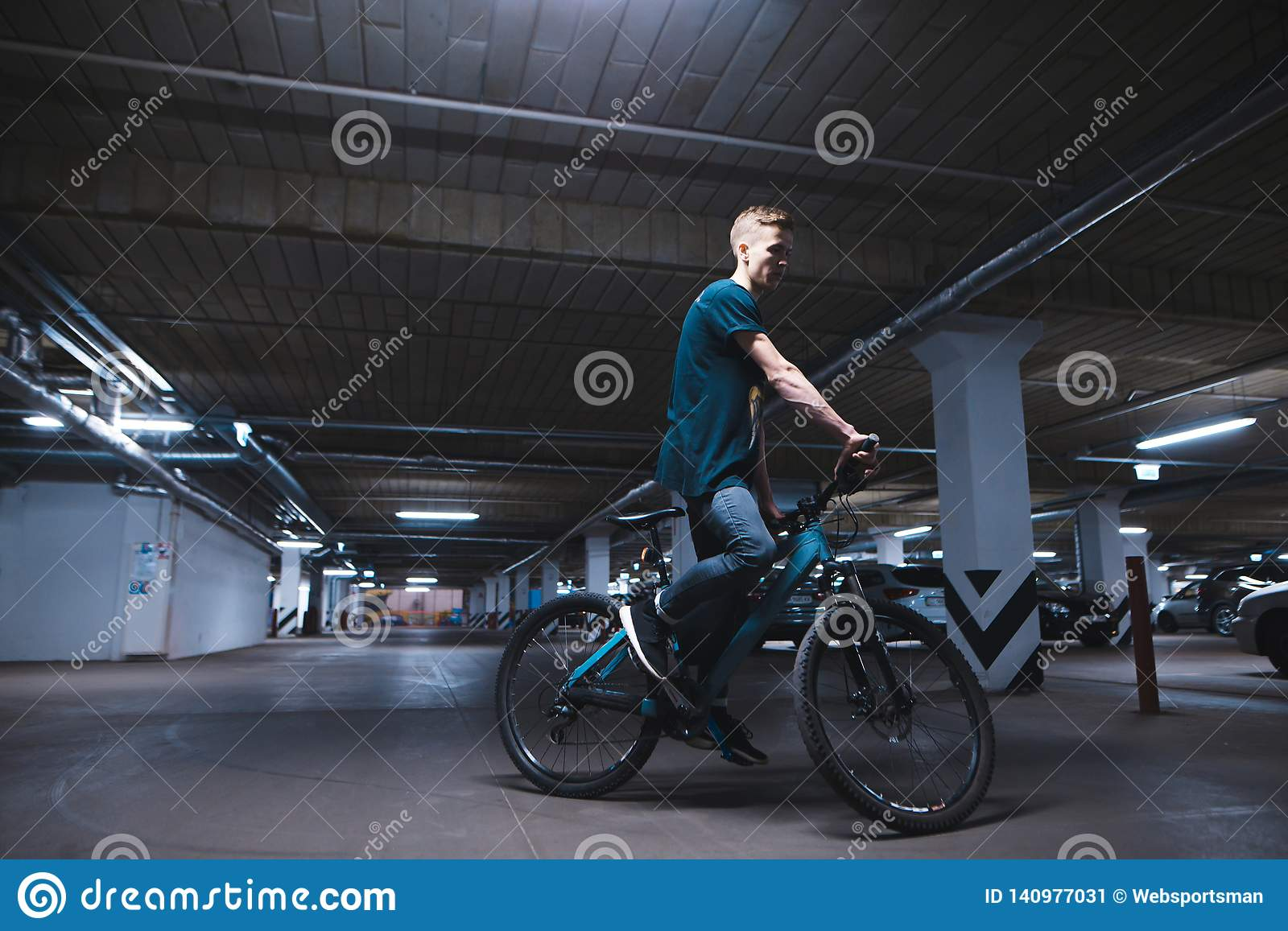 cyclist in an underground parking lot for cars. A man rides a bicycle by parking