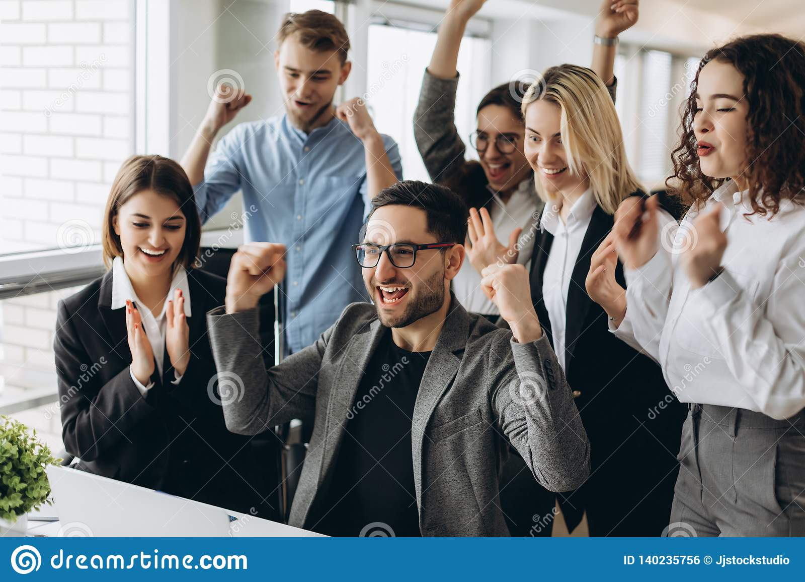 Portrait d équipe faisante des gestes expressive réussie très heureuse d affaires au bureau