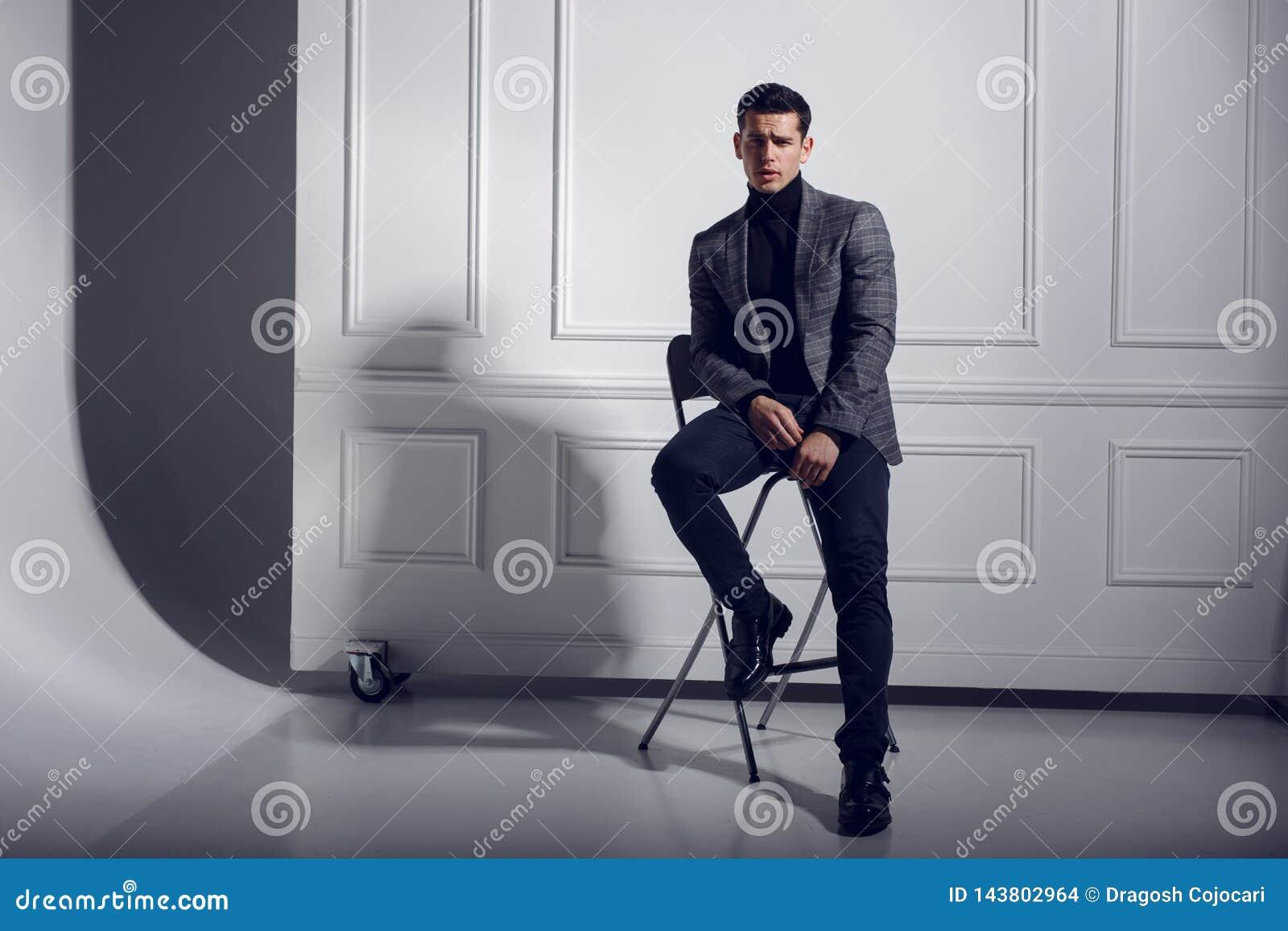 Portrait d attrayant, d une manière élégante hommes dans le costume gris et verres, posant dans le studio sur le fond blanc