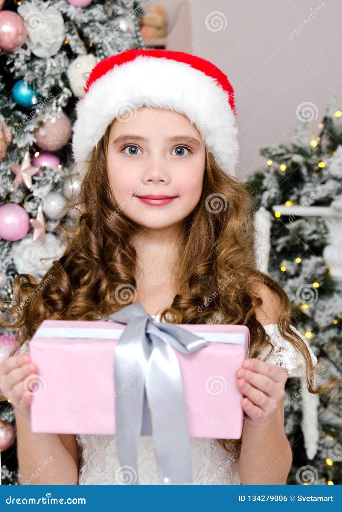 Portrait d enfant de sourire heureux adorable de petite fille dans le boîte-cadeau de participation de chapeau de Santa près de l