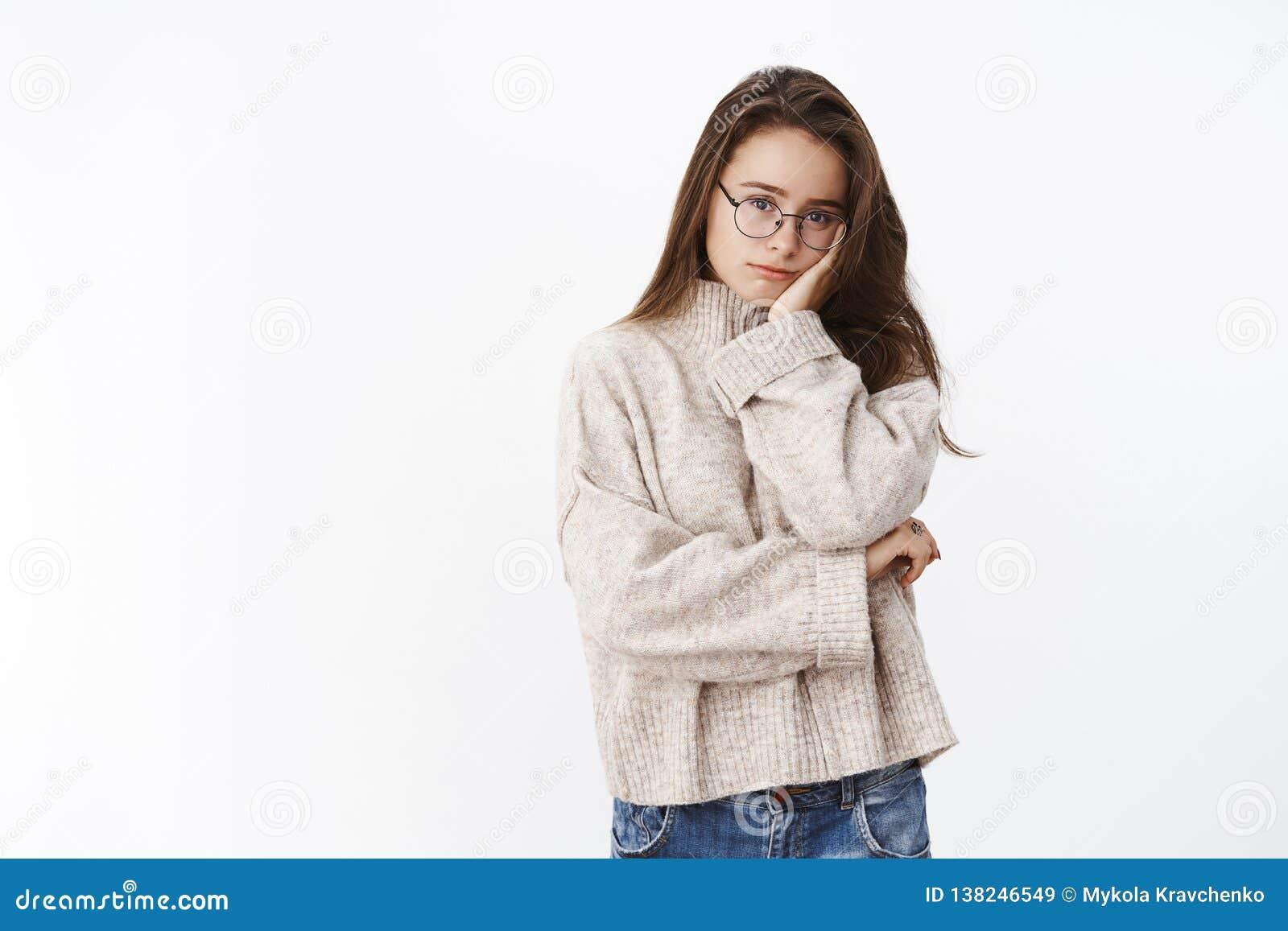 Portrait d indépendant féminin mignon fatigué et vidangé en verres de chandail et de PC se penchant la tête sur la paume semblant