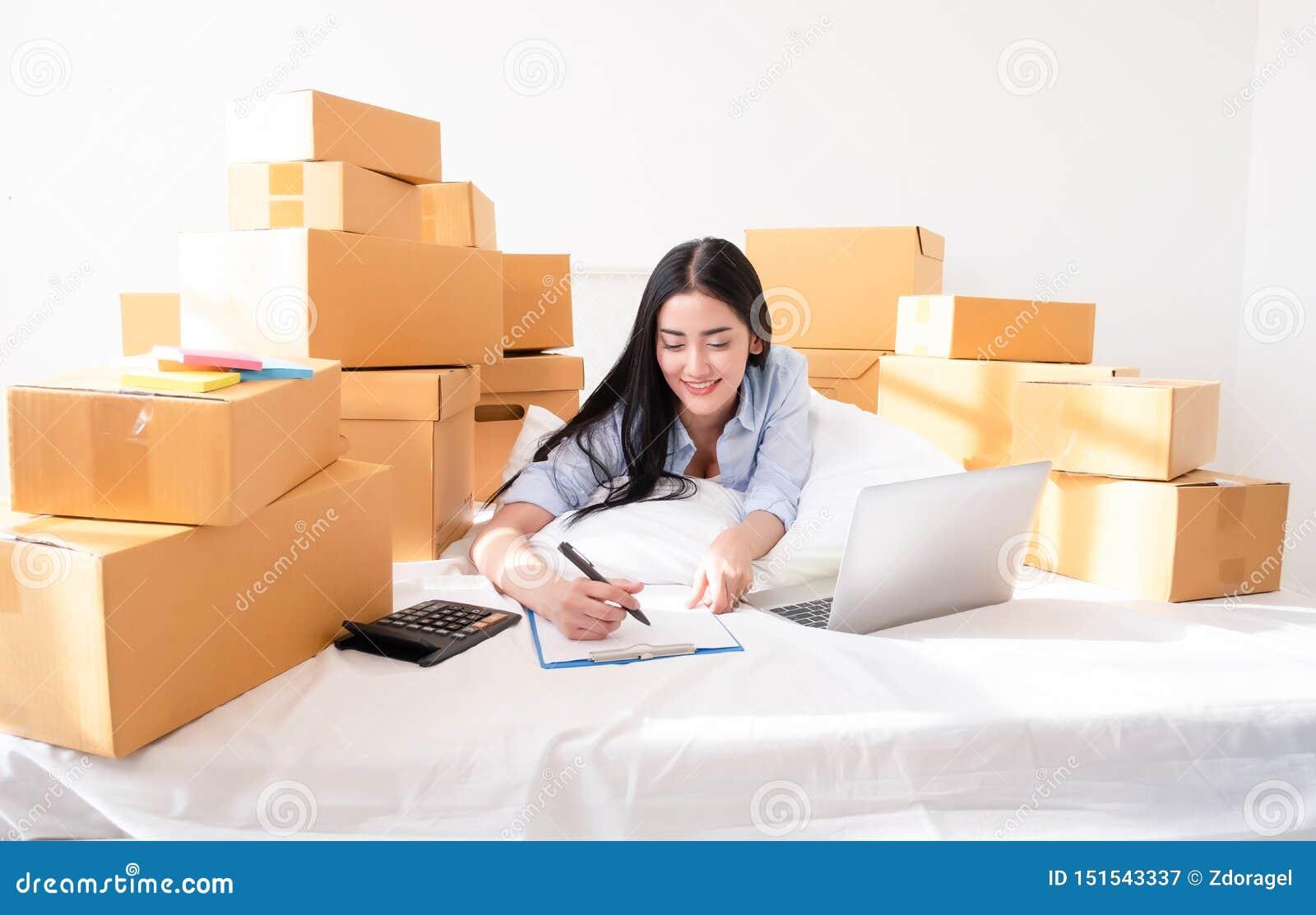 Portrait d ordinateur portable fonctionnant de jeune femme asiatique avec le colis postal sur le lit à la maison, vendant des idé