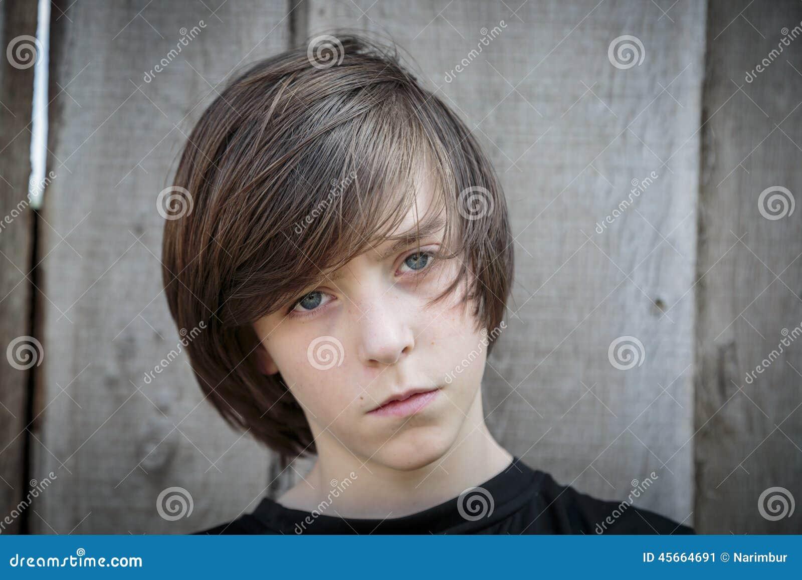 Portrait d un adolescent devant un fond en bois