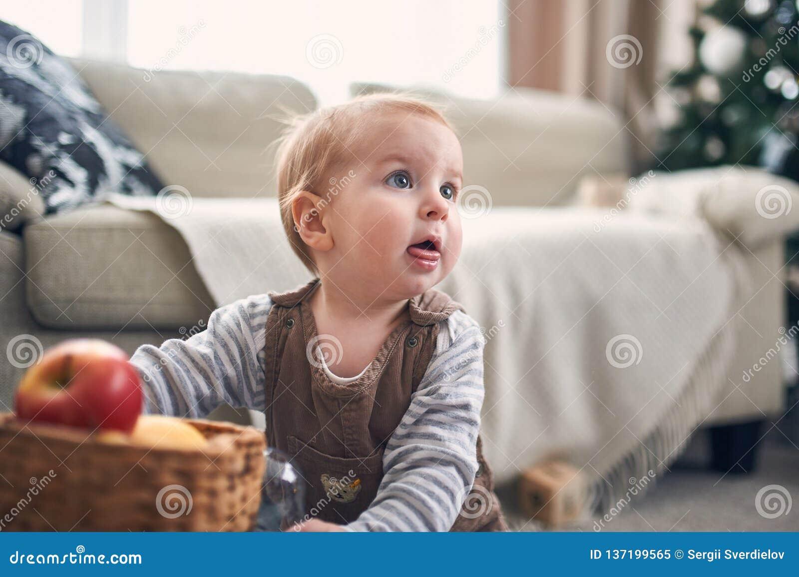 Portrait d un bébé garçon de 1 an mignon s asseyant sur le plancher décorations de Noël sur un fond