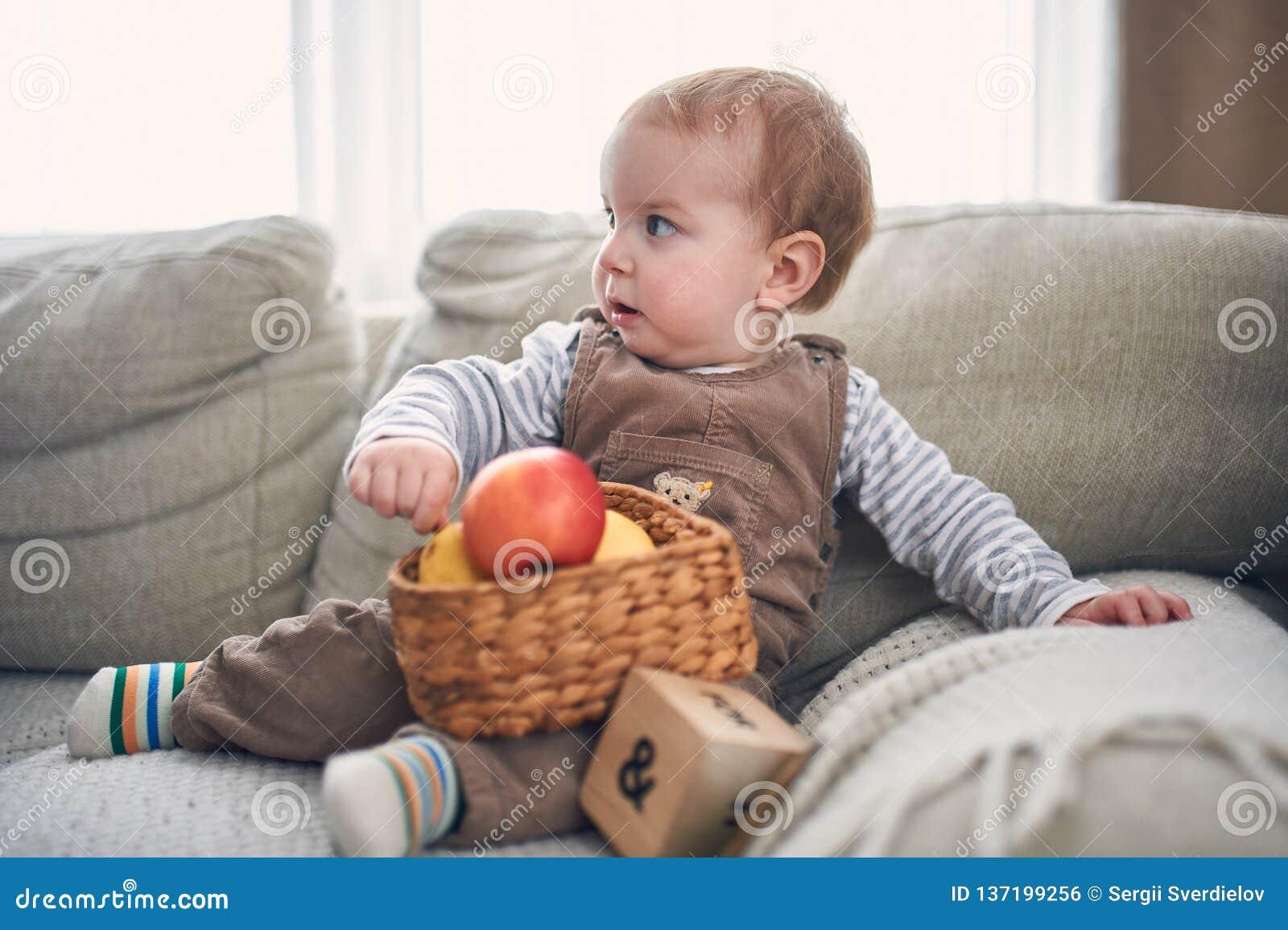 Portrait d un bébé garçon de 1 an mignon s asseyant sur un sofa