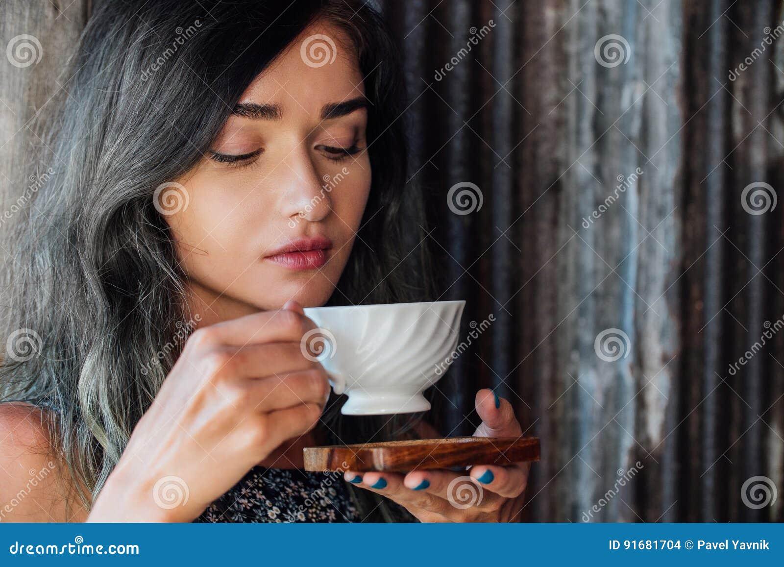 Portrait d un café potable de fille dans un café de vintage sur la terrasse en Asie Reniflements, boissons