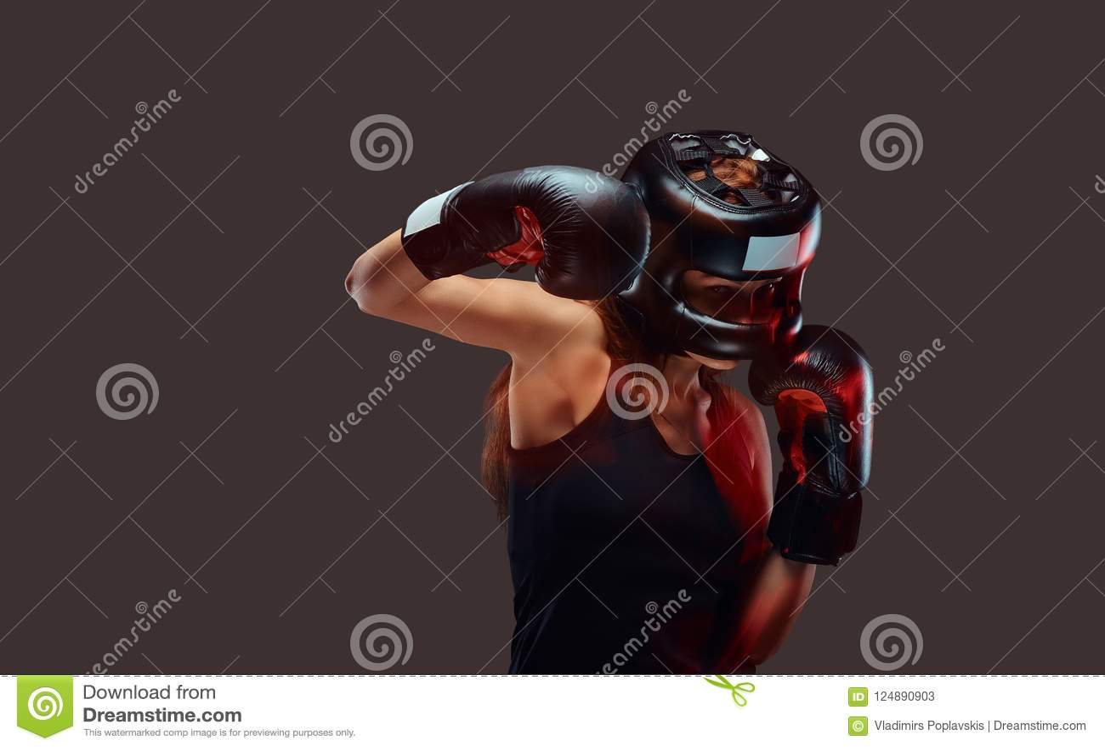 Portrait d un casque de protection de port et des gants de boxeur féminin pendant les exercices de boxe, concentré sur le process