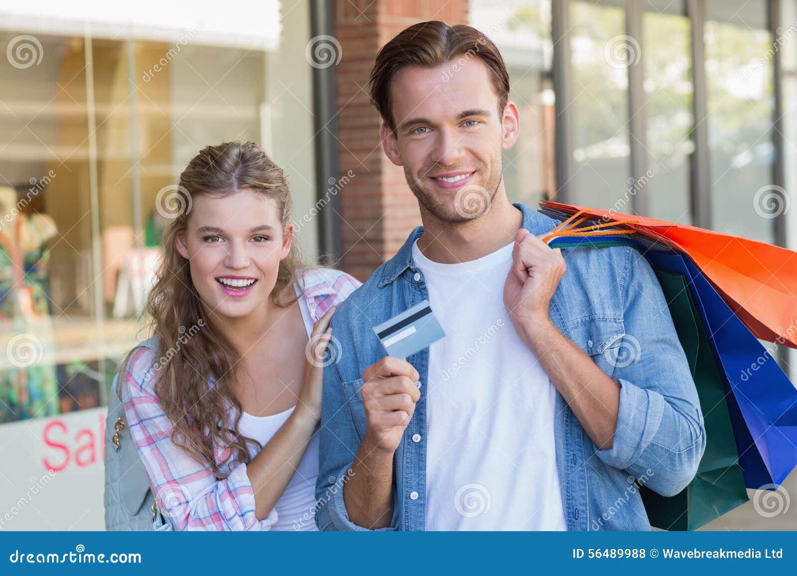 Portrait d un couple heureux montrant leur nouvelle carte de crédit