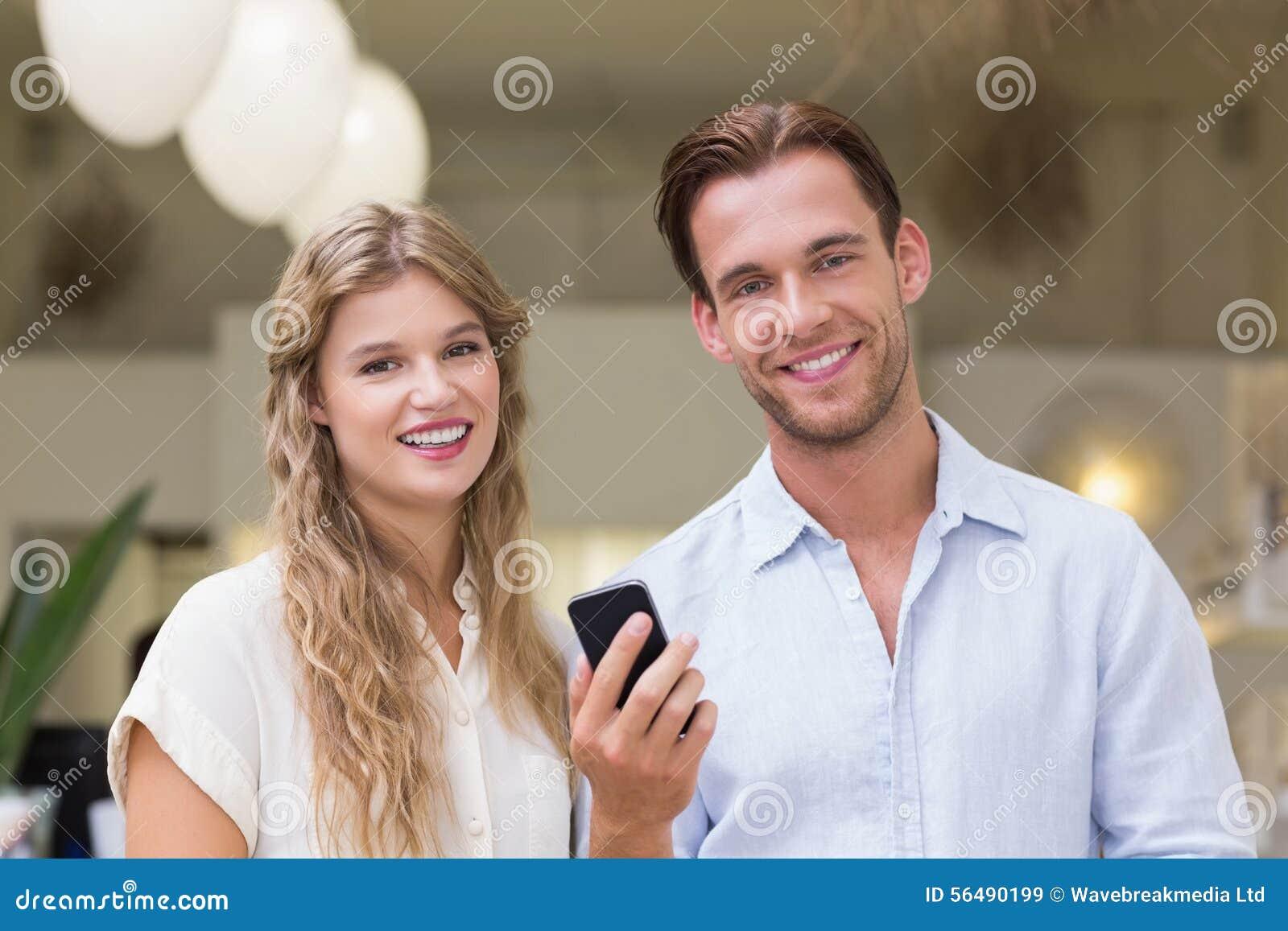 Portrait d un couple heureux regardant le smartphone