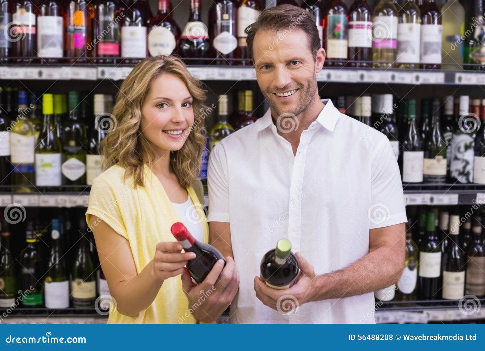Portrait d un couple occasionnel de sourire regardant la bouteille de vin
