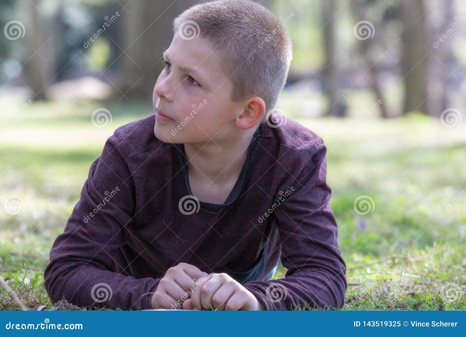 Portrait d un garçon se trouvant sur l herbe dans le jardin un jour d été regardant au côté