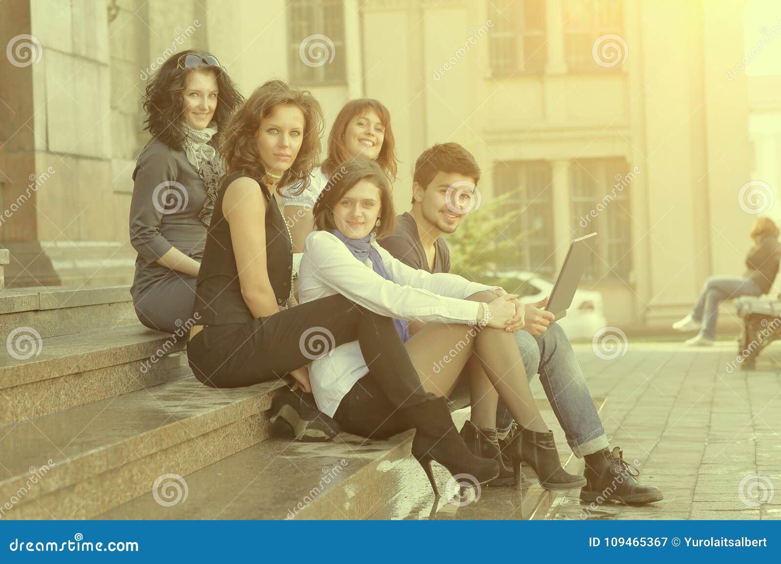 Portrait d un groupe d étudiants s asseyant devant l université